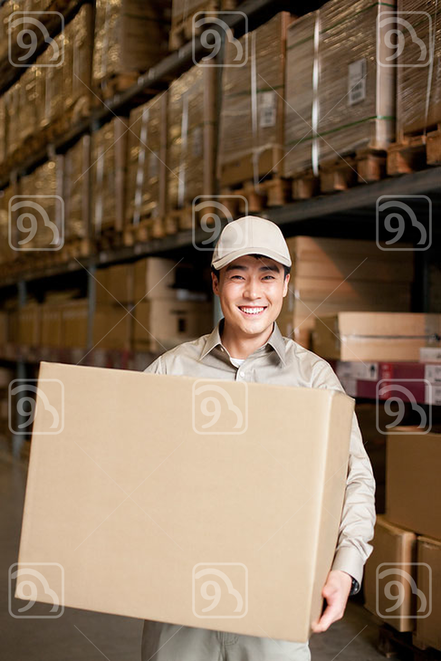 Male Chinese warehouse worker carrying a box