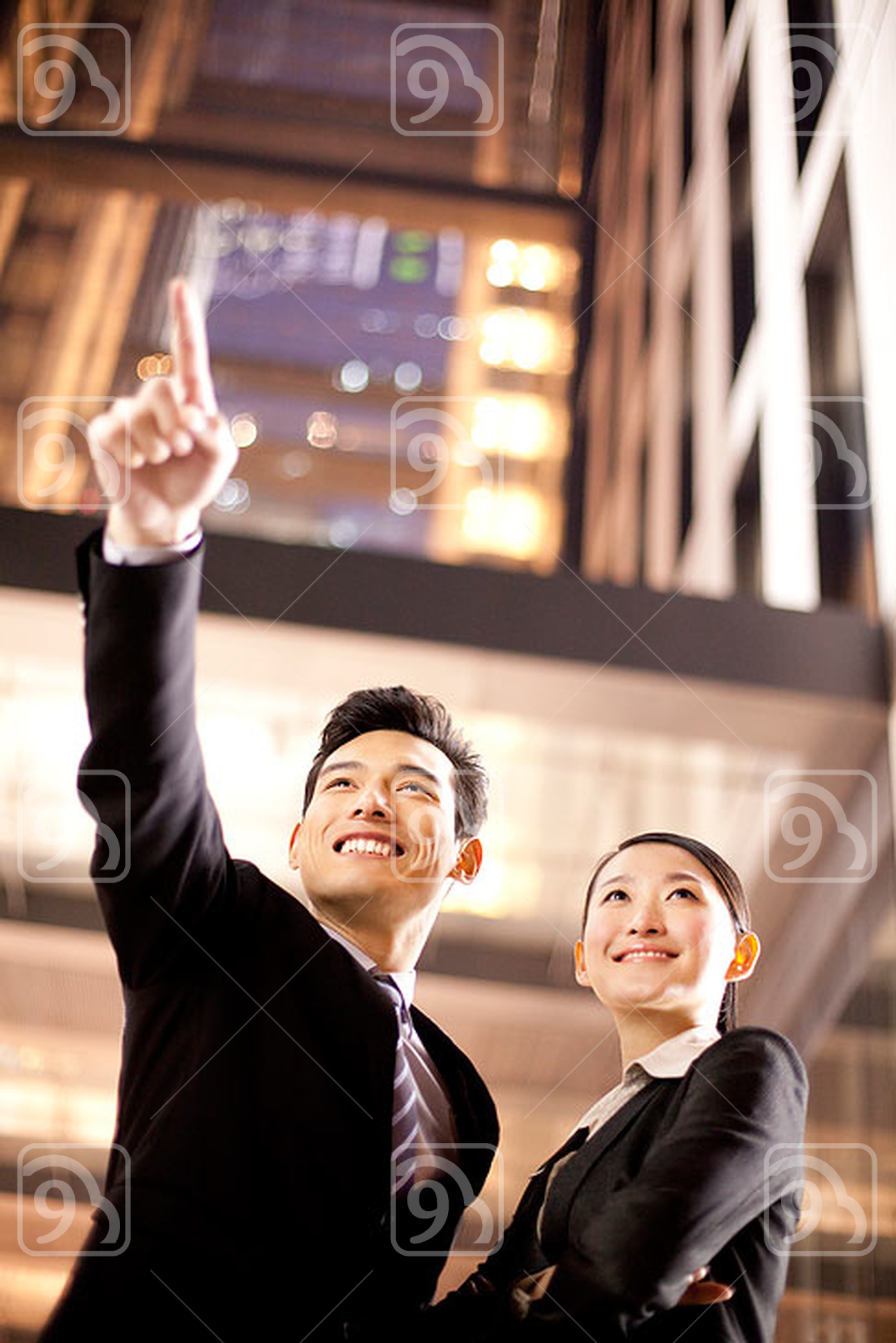 A Chinese businessman and businesswoman outside an office building at night