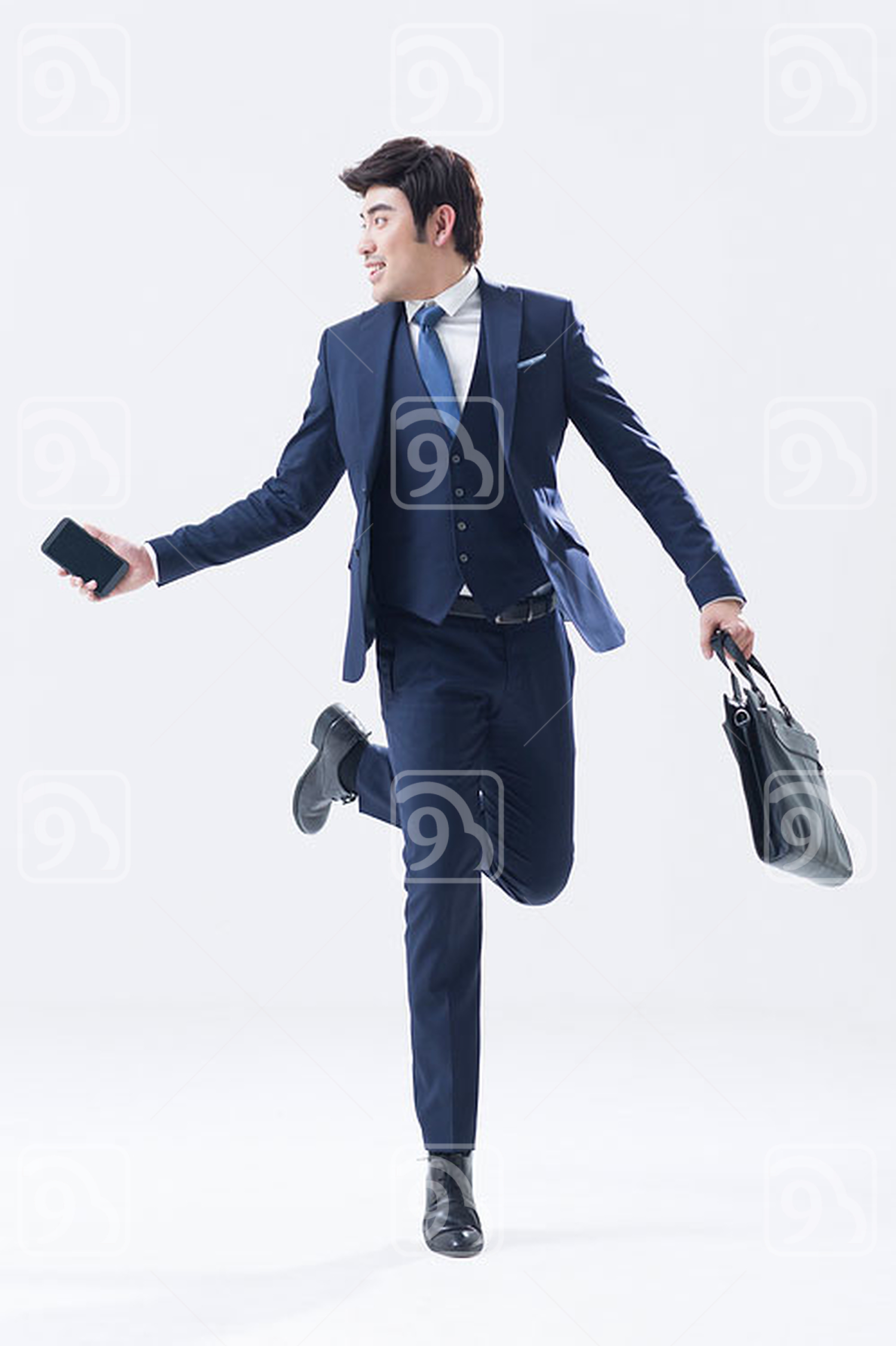 Young Chinese businessman running with briefcase and smart phone