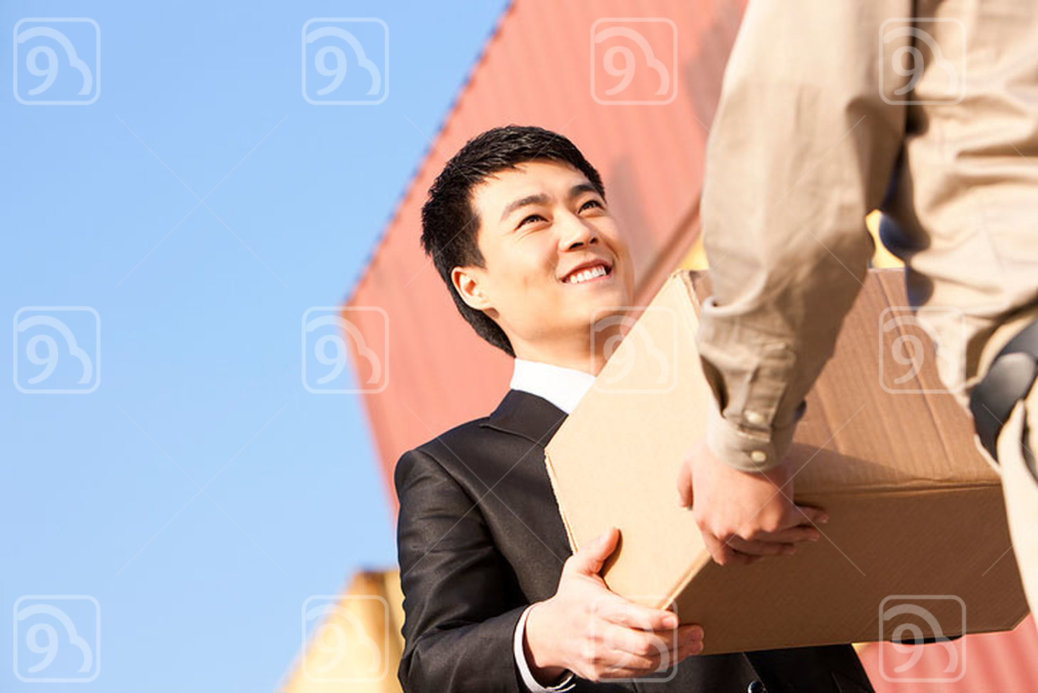 Chinese businessman and shipping industry worker giving and receiving a cardboard box