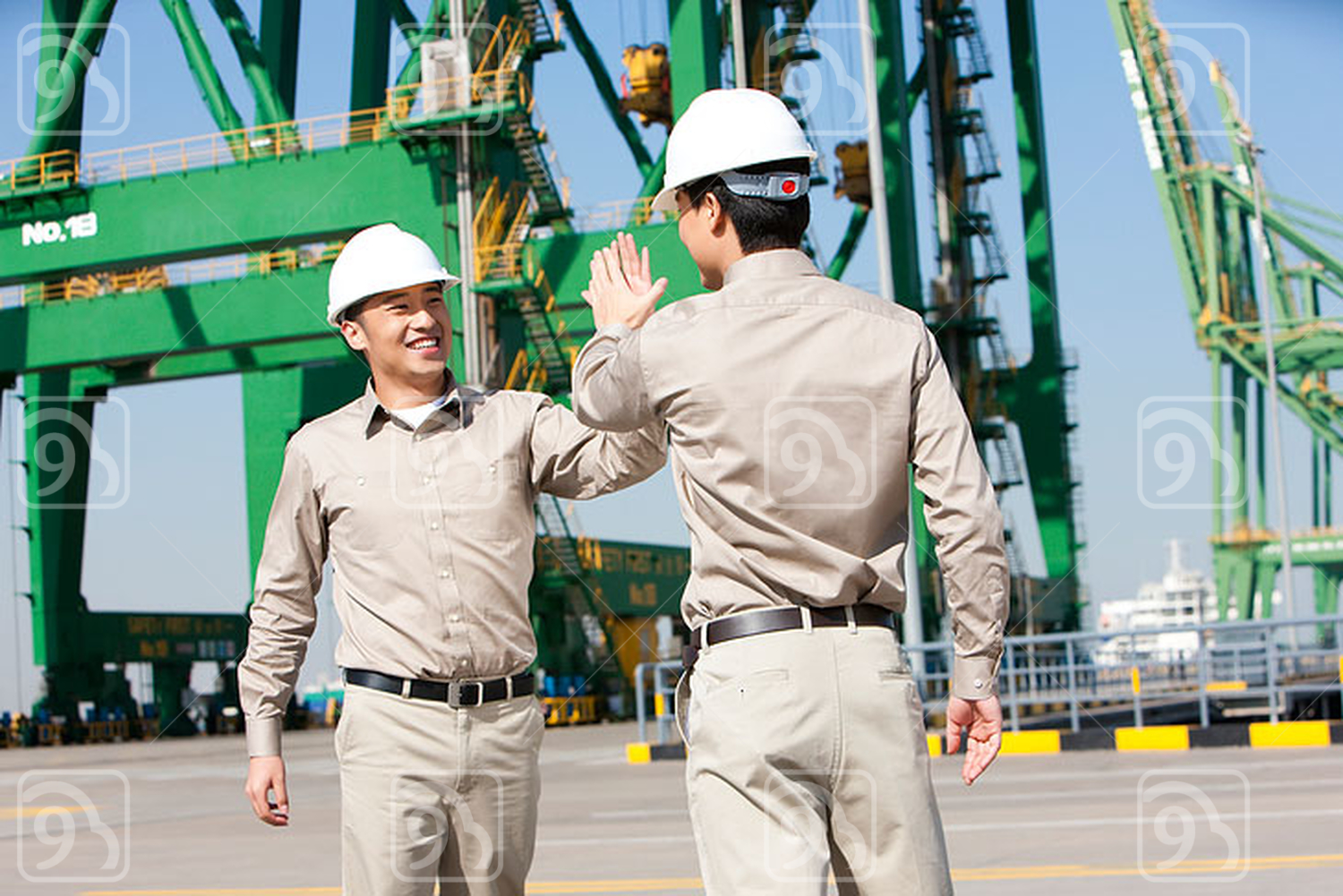 Male Chinese shipping industry workers high-fiving