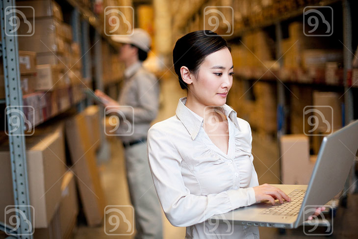 Chinese businesswoman in a warehouse using a laptop
