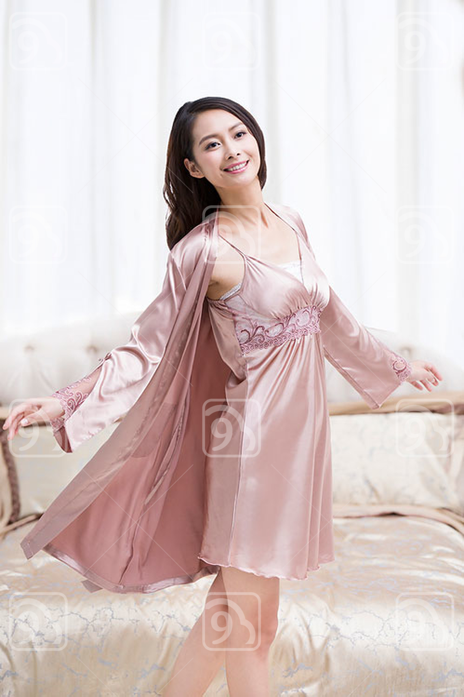 Happy young Chinese woman in bedroom