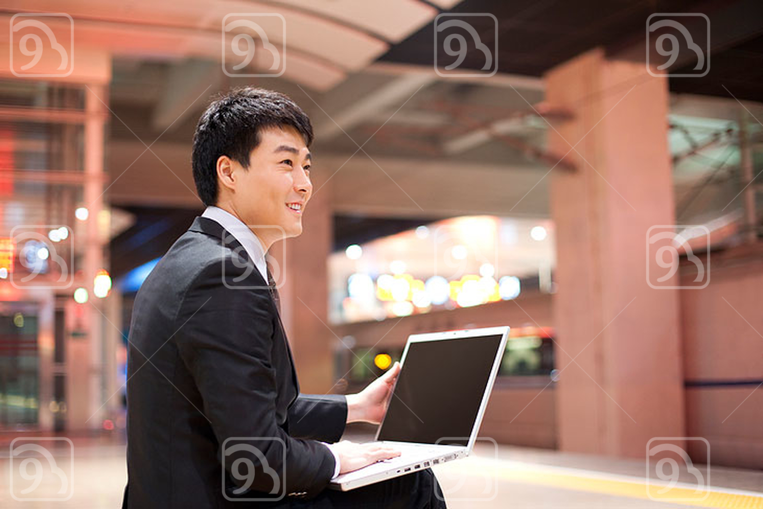 Young Chinese businessman using his laptop at the train station