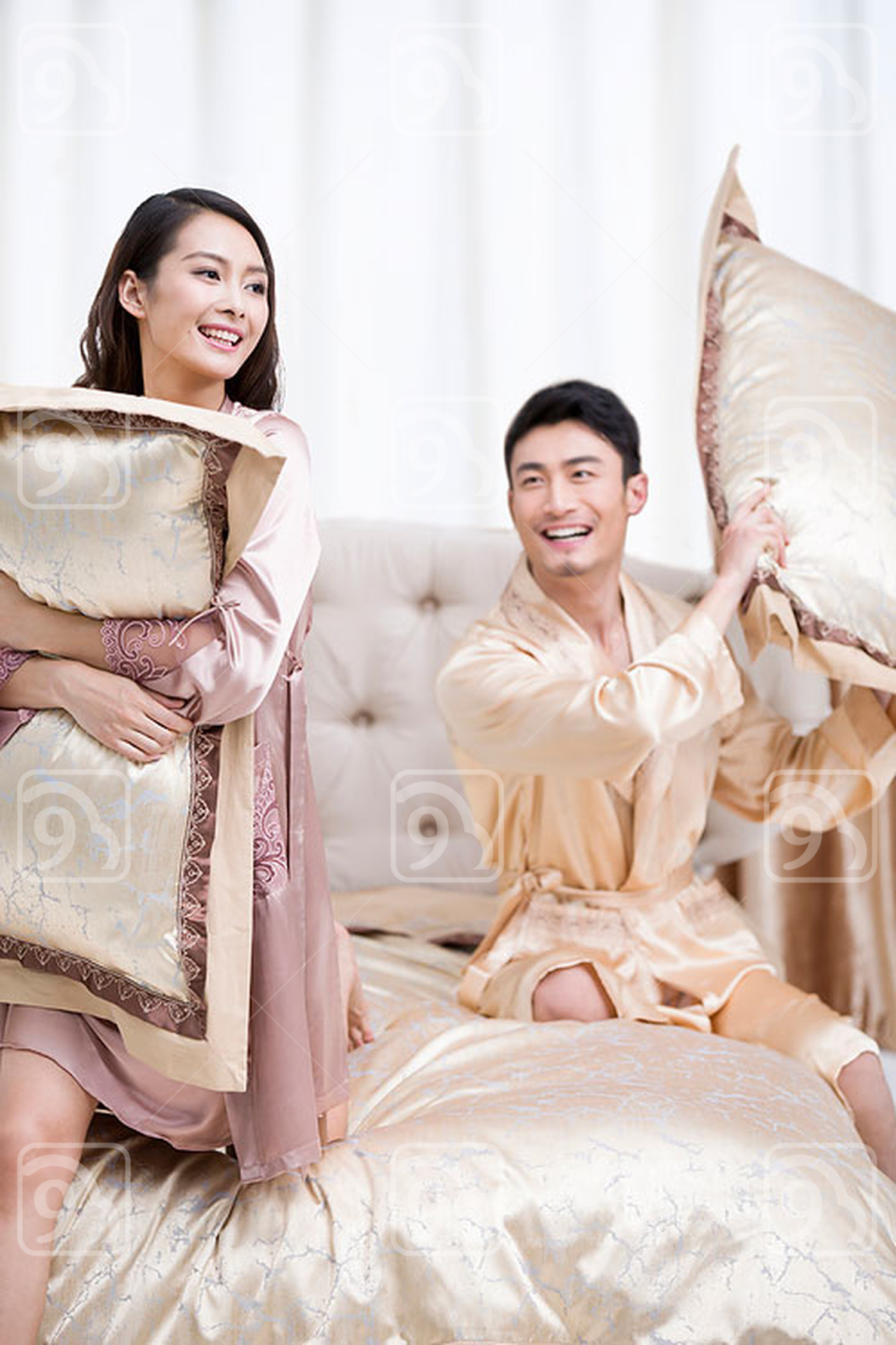 Young Chinese couple having pillow fight in bedroom