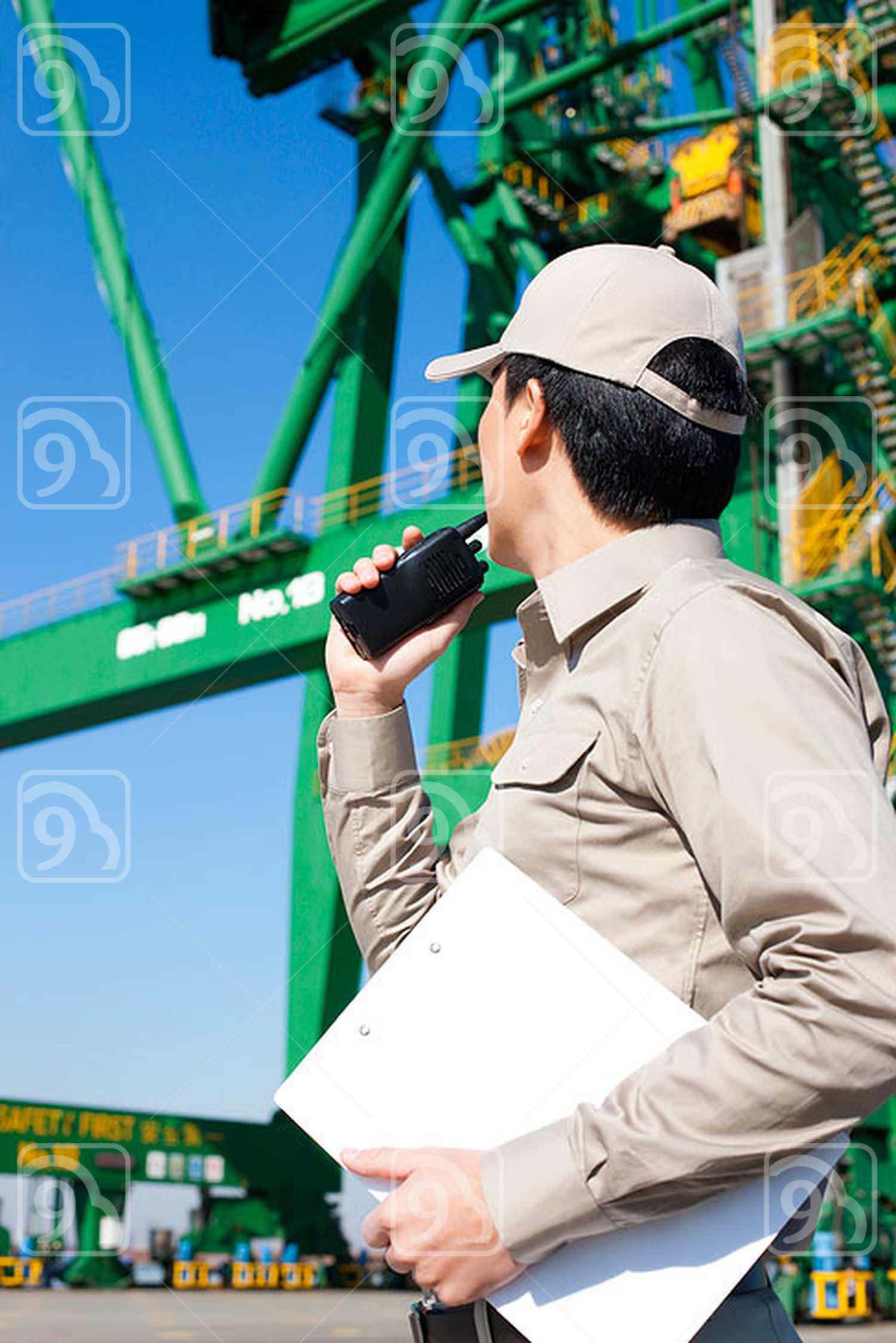 Male Chinese shipping industry worker talking on walkie-talkie with crane in the background