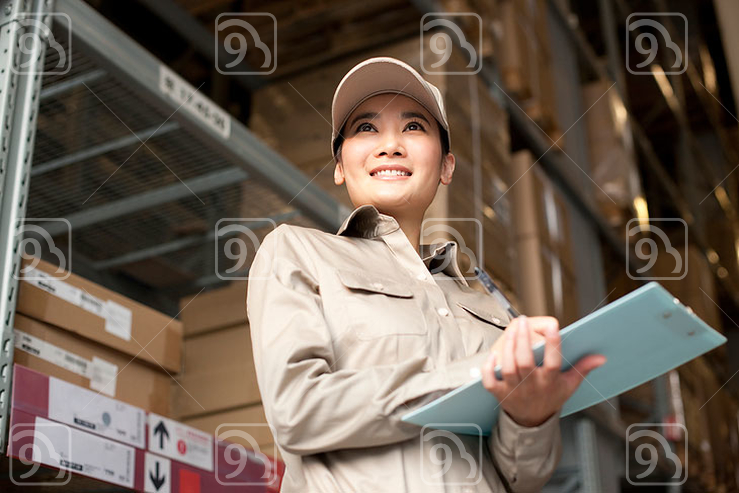 Female Chinese warehouse worker with clipboard