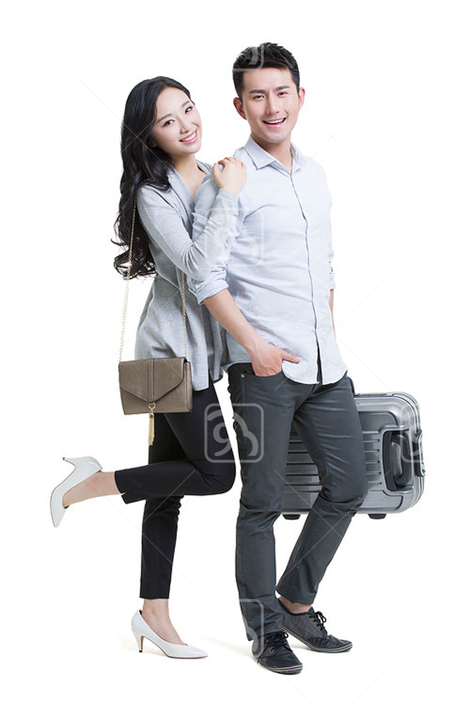 Happy young Chinese couple traveling with luggage