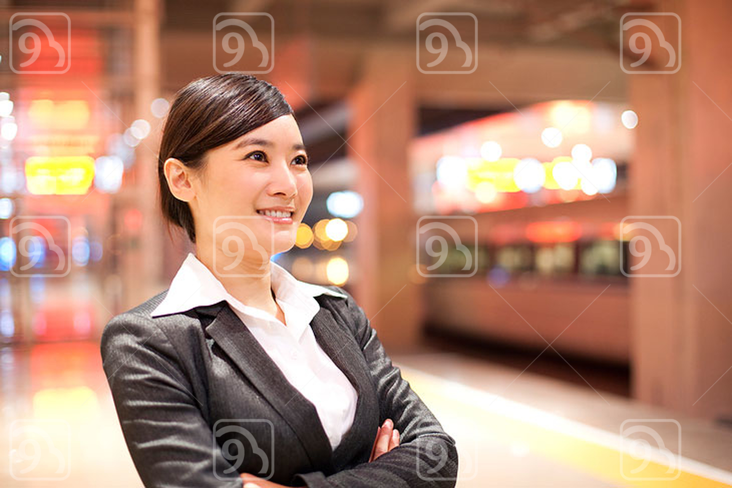 Young Chinese businesswoman contemplating at the train station