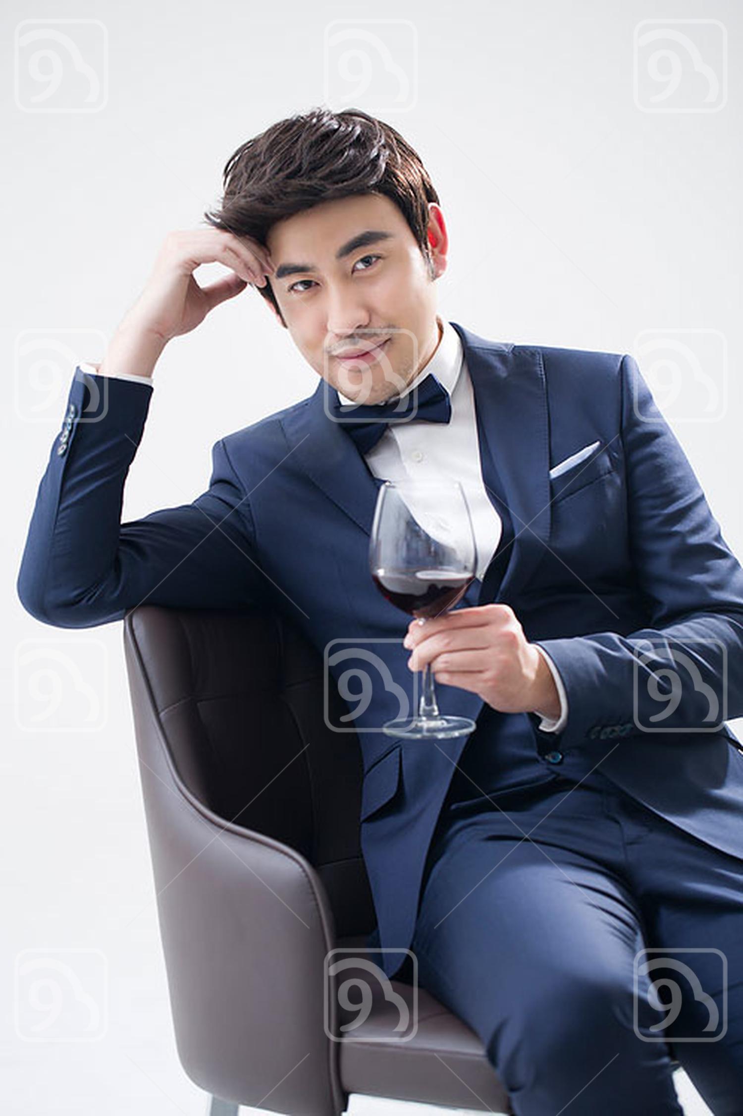 Elegant young Chinese man enjoying red wine