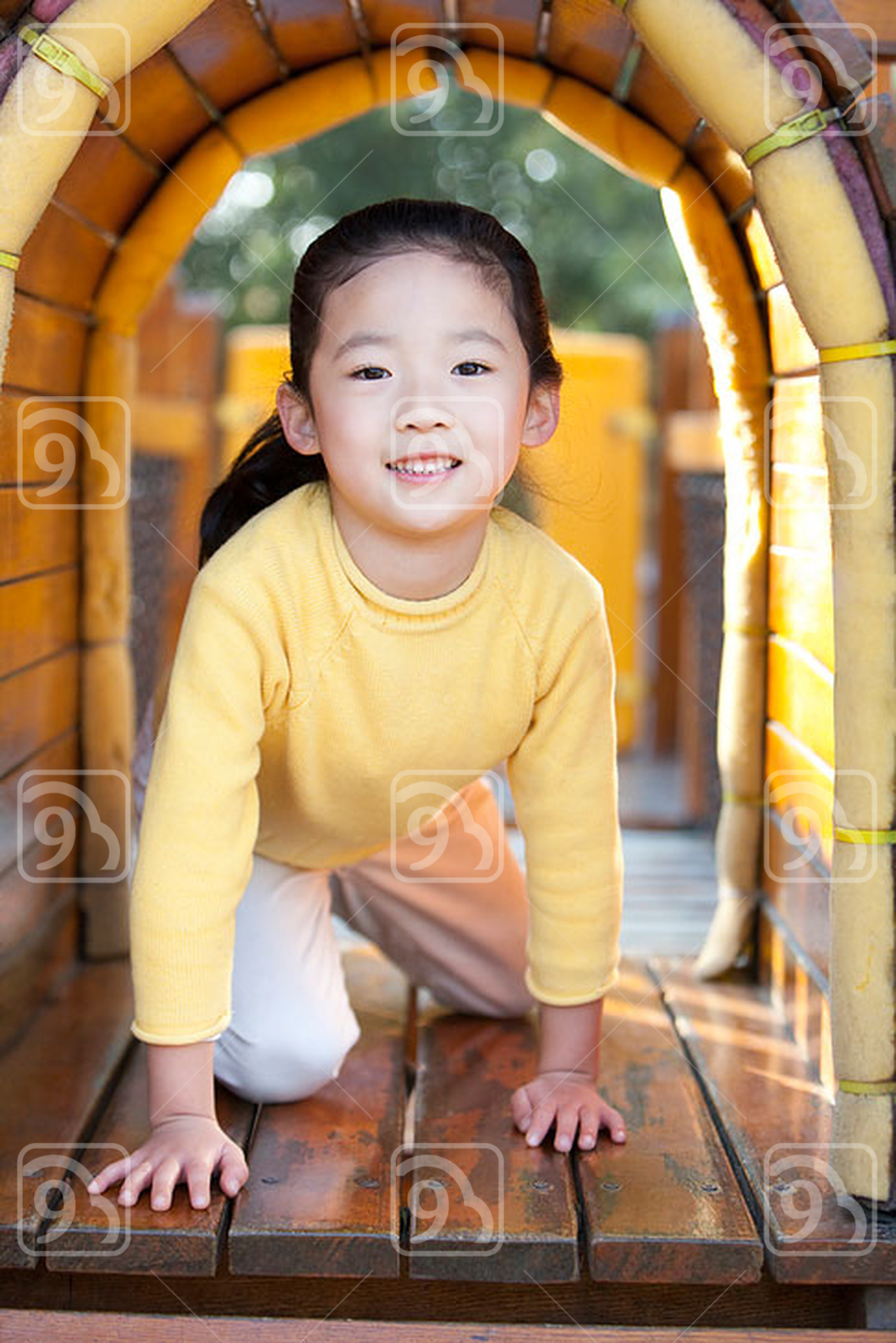 Chinese girl crawling through tunnel in playground