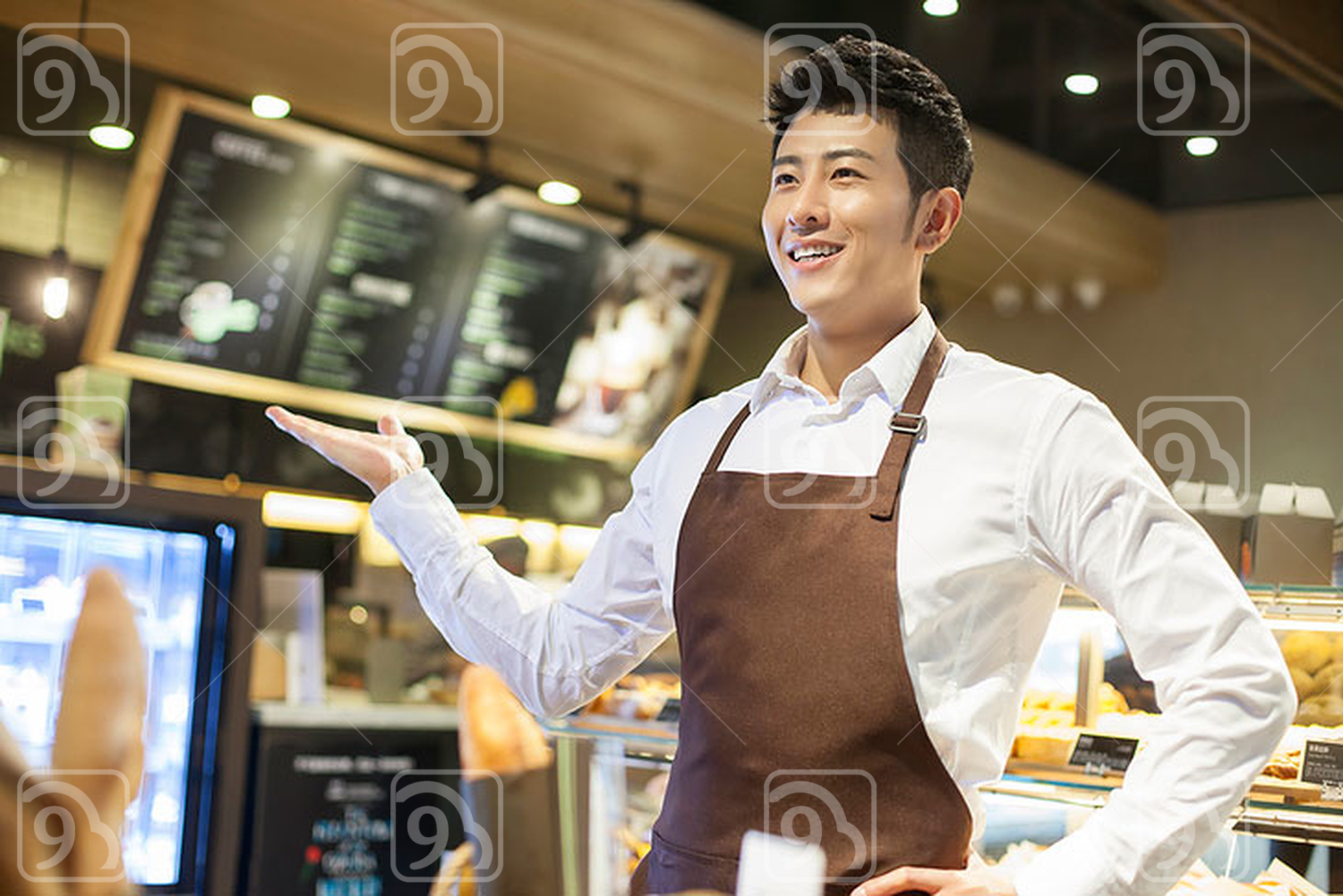Young Chinese man working in bakery