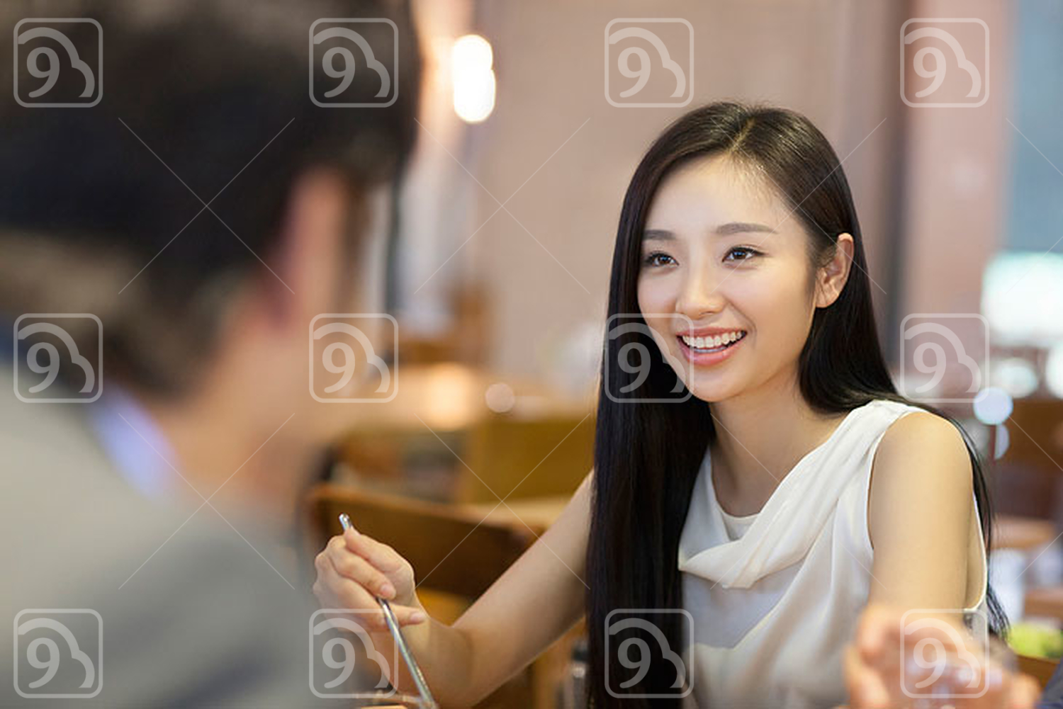 Young Chinese woman having dinner with friends
