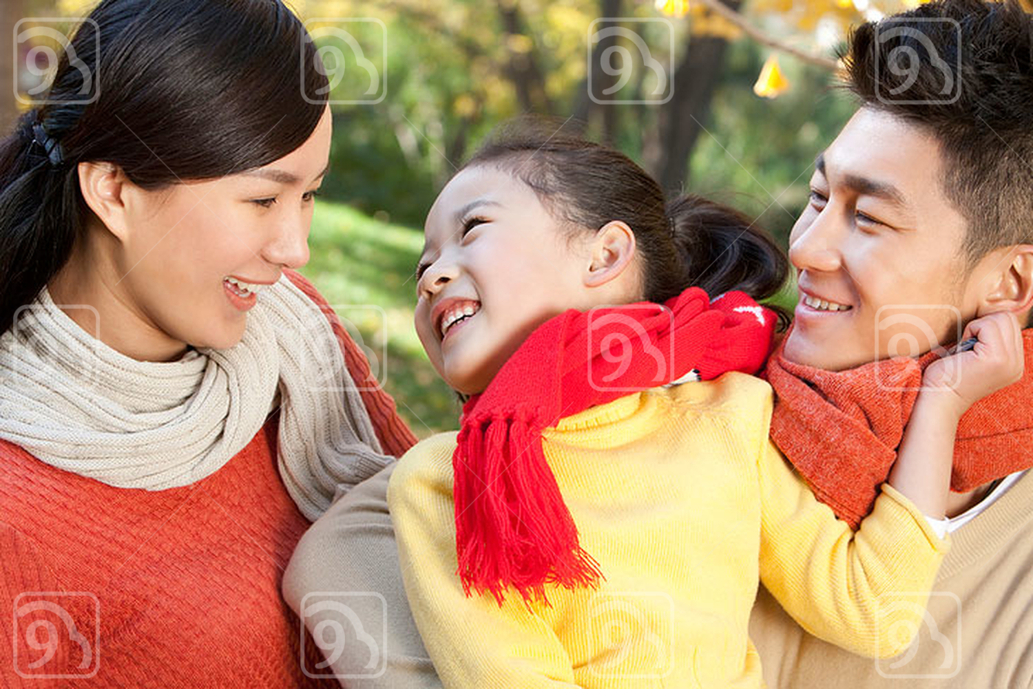 Young Chinese family in a park in autumn