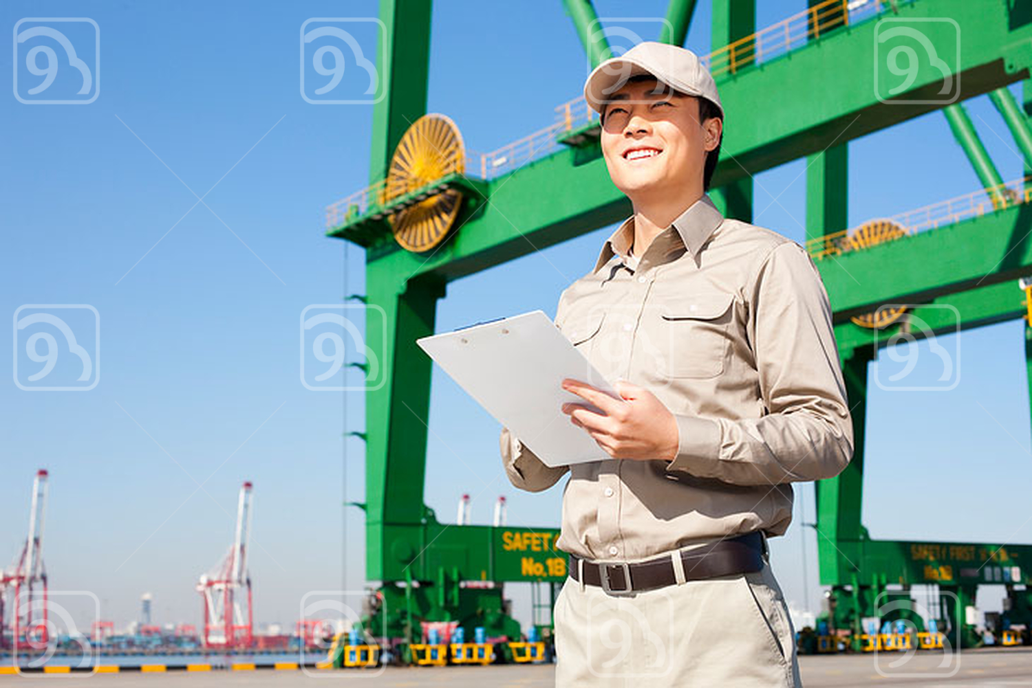 Male Chinese shipping industry worker with shipping dock and crane in the background