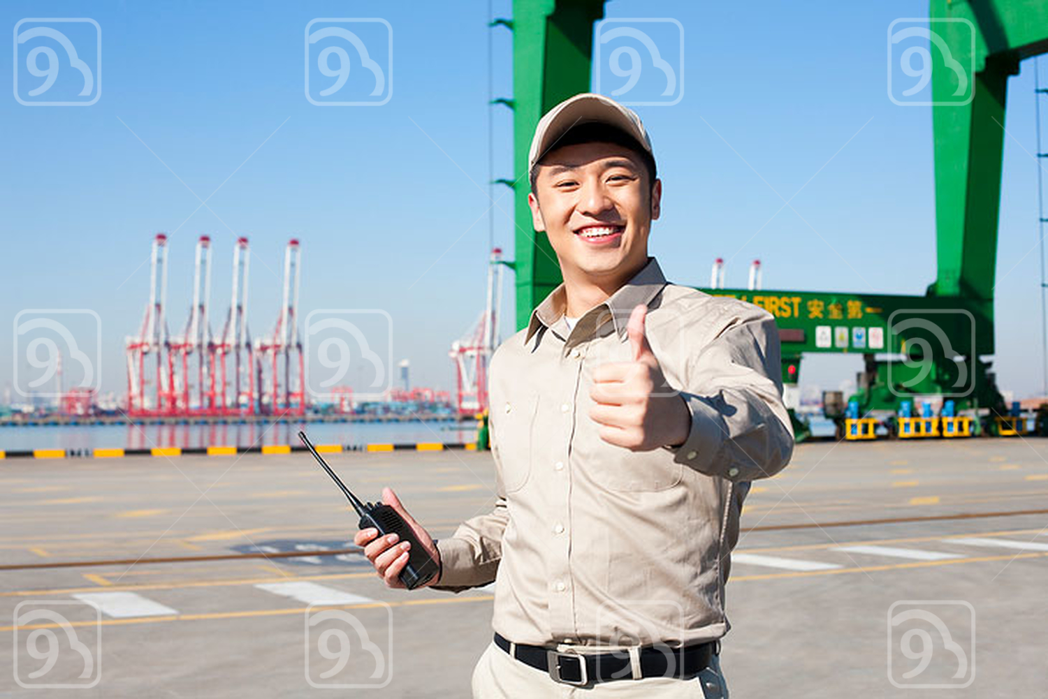 Male Chinese shipping industry worker with walkie talkie giving the thumbs-up