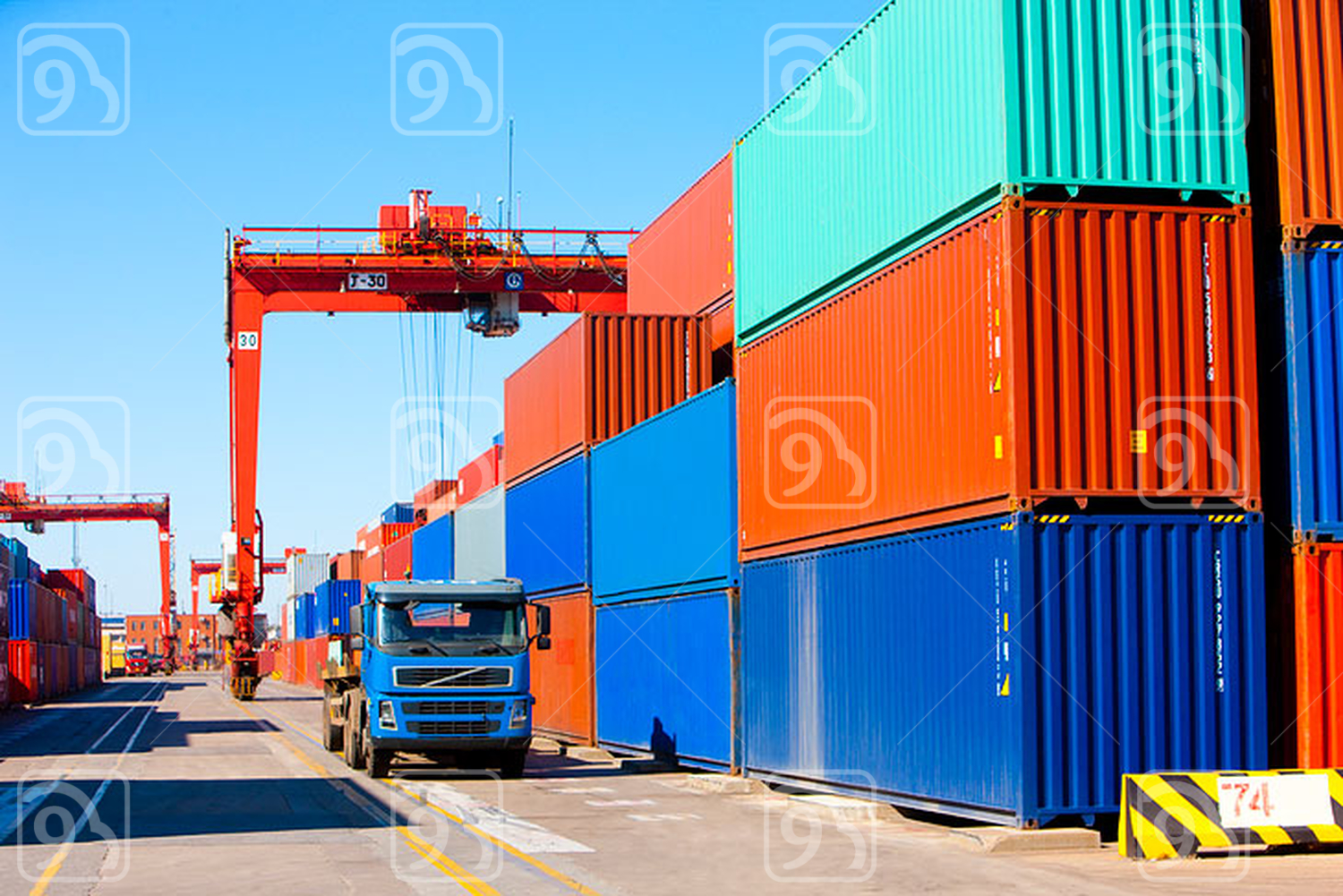 Cranes, trucks and cargo containers in shipping dock