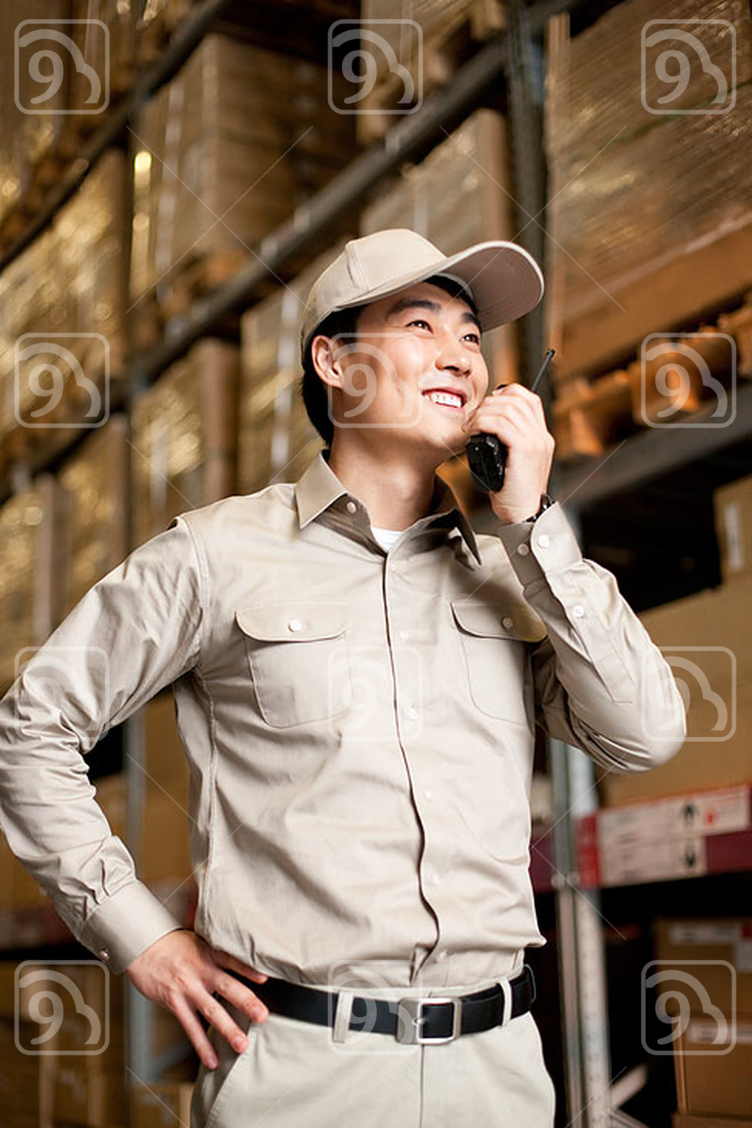 Male Chinese warehouse worker with walkie-talkie