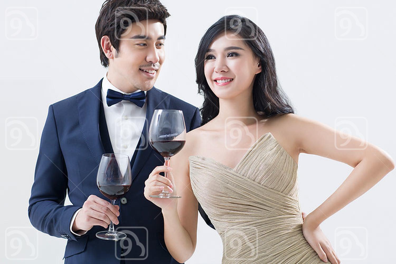 Elegant young Chinese couple enjoying red wine