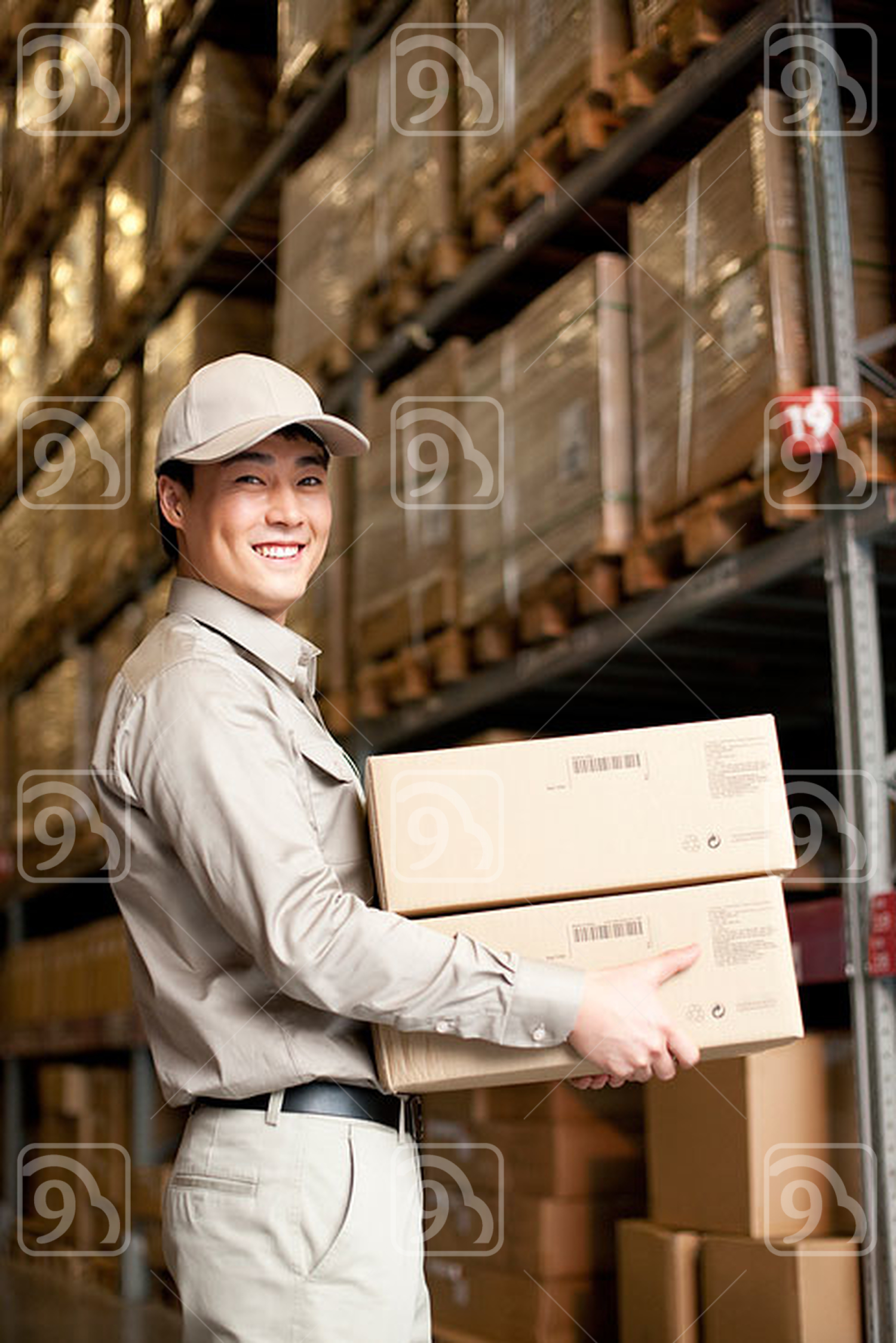 Male Chinese warehouse worker carrying boxes