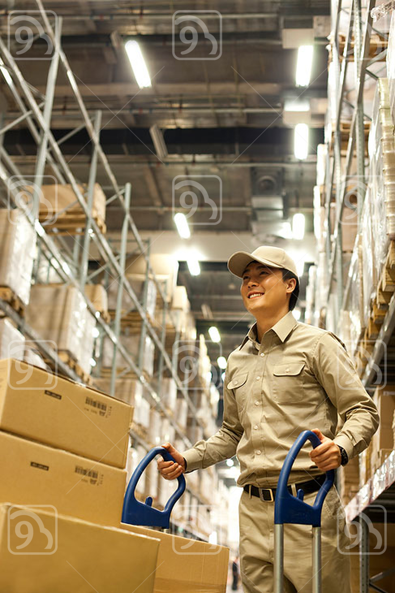 Male Chinese warehouse worker pushing boxes