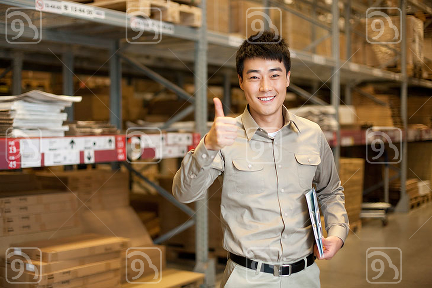 Male Chinese warehouse worker giving the thumbs up
