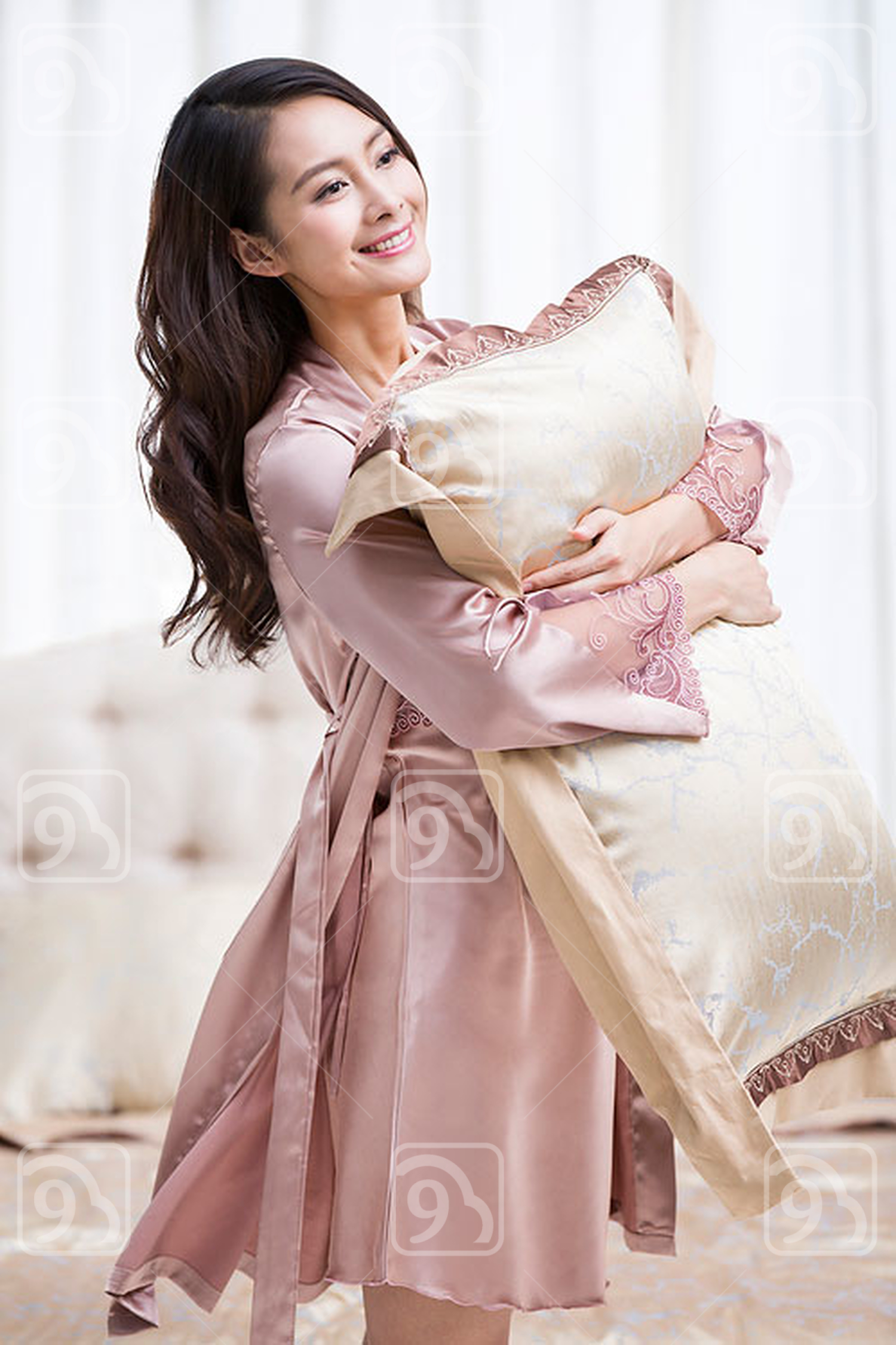 Happy young Chinese woman holding a pillow