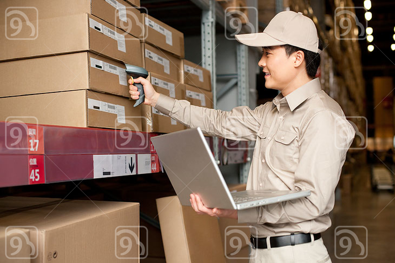 Male Chinese warehouse worker with laptop and scanner