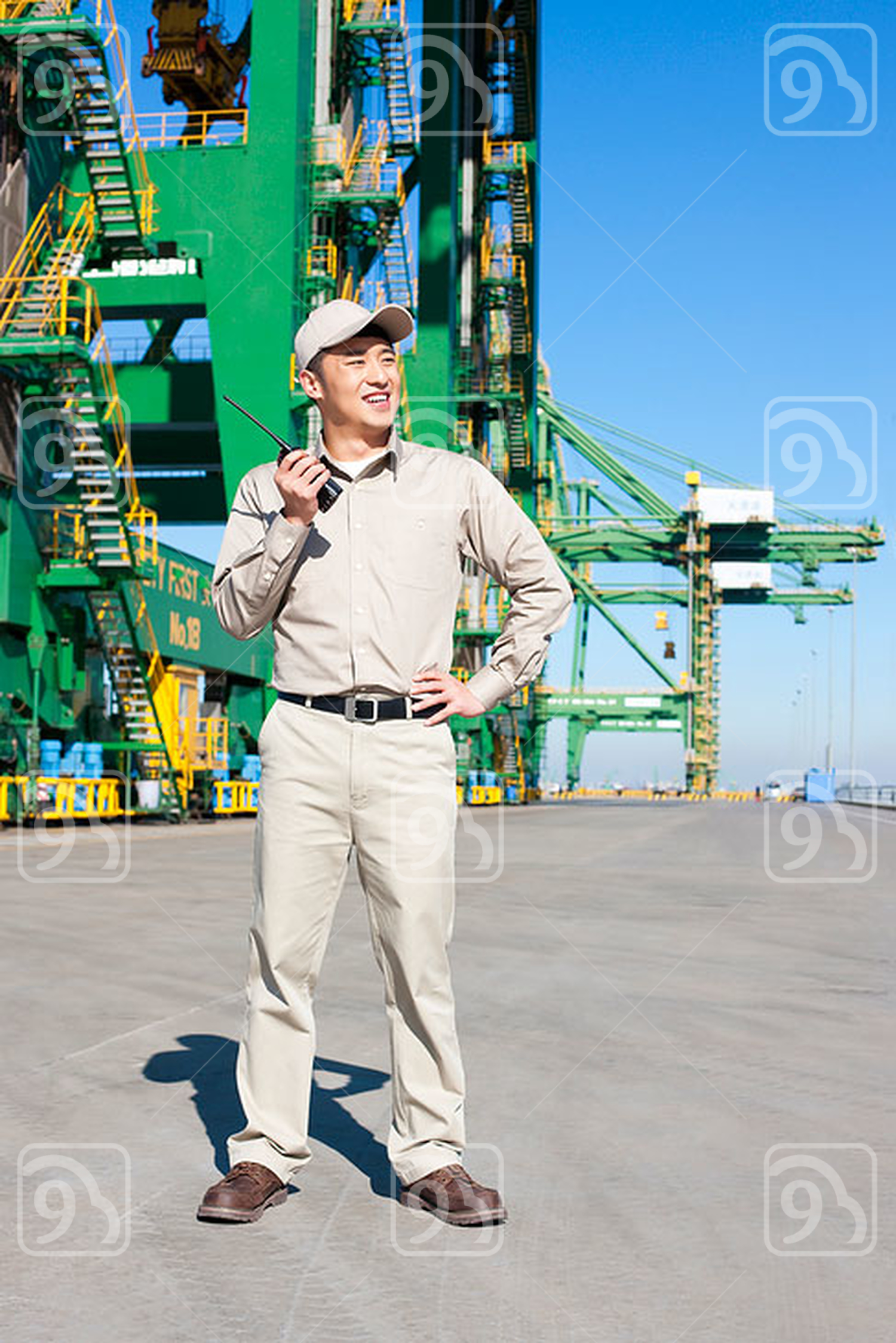 Male Chinese shipping industry worker with walkie talkie and crane in the background