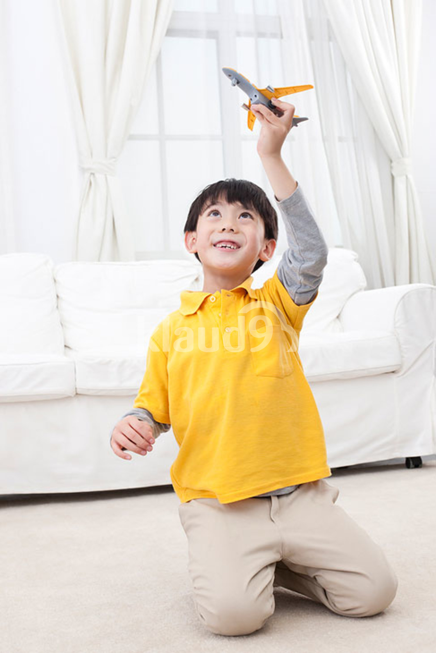 Little Chinese boy playing toy plane