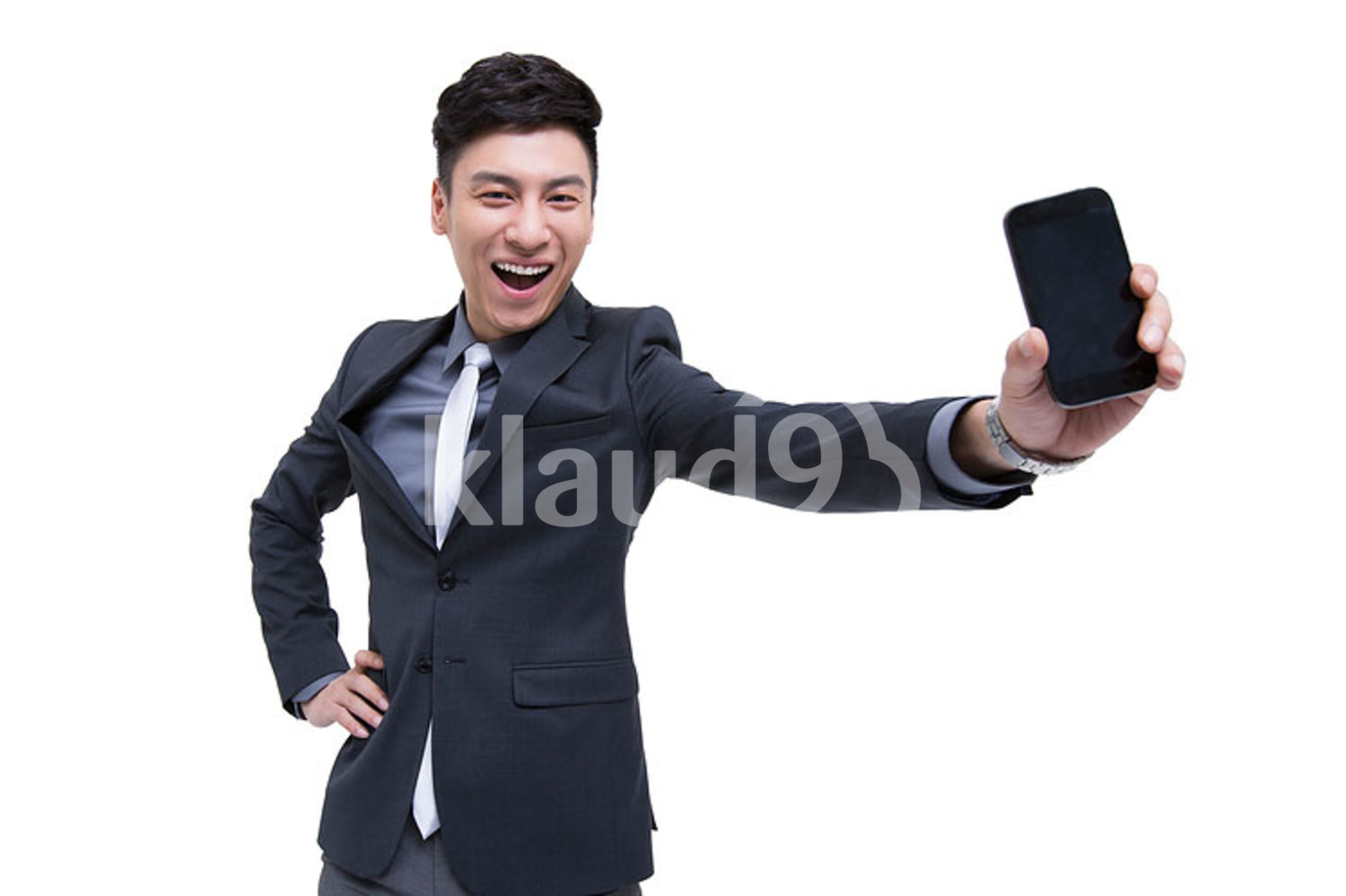 Cheerful Chinese businessman being proud of his smart phone