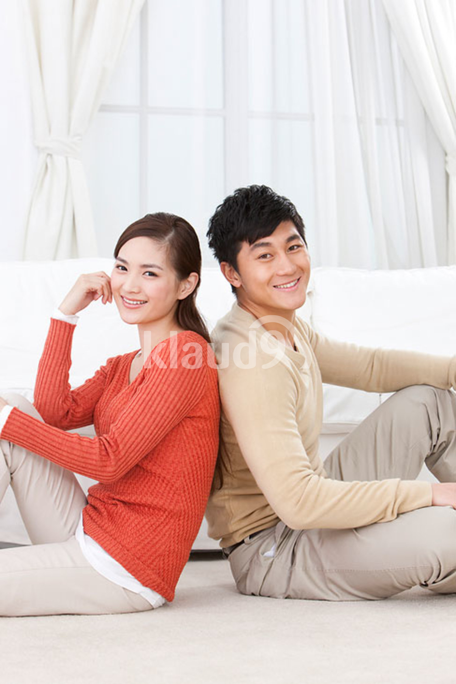 Happy young Chinese couple sitting on carpet