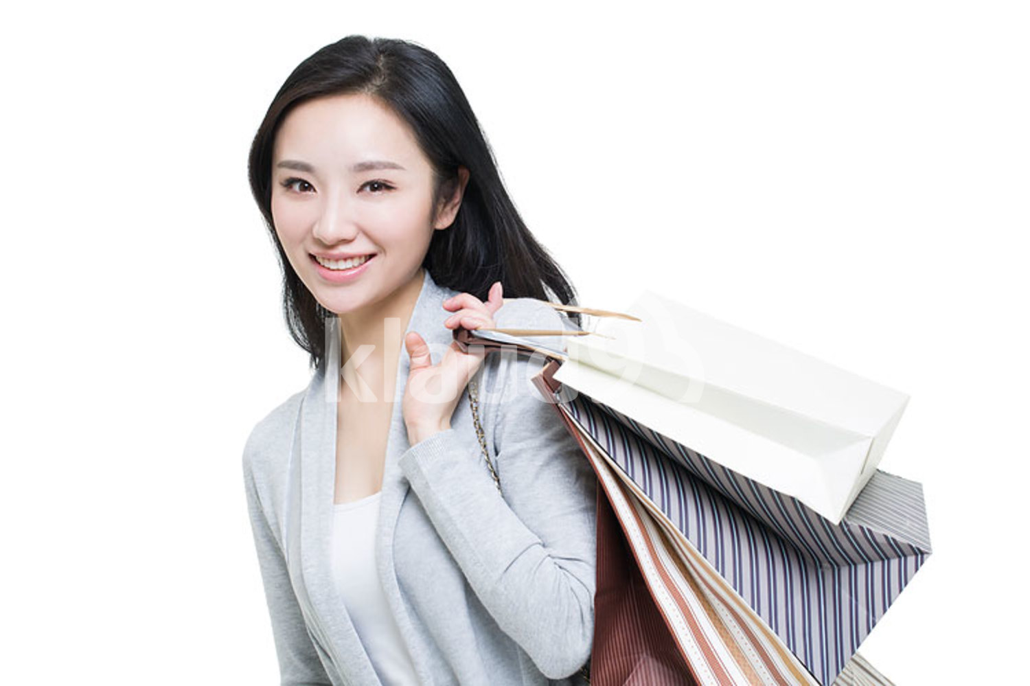 Happy young Chinese woman with shopping bags