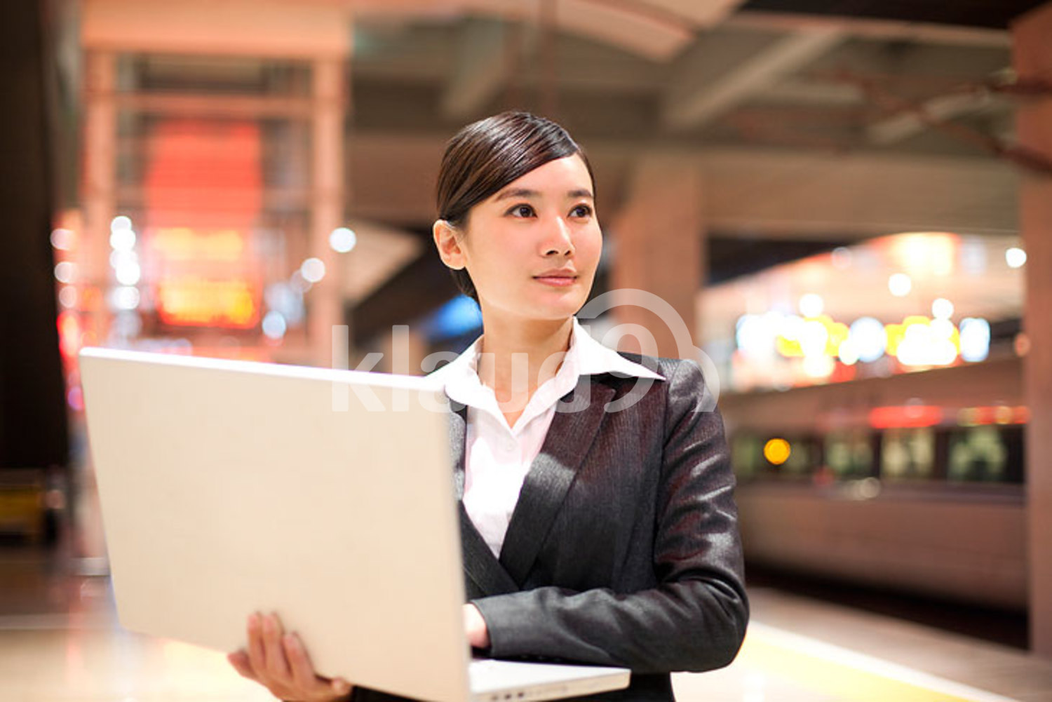 Young Chinese businesswoman using her laptop at the train station