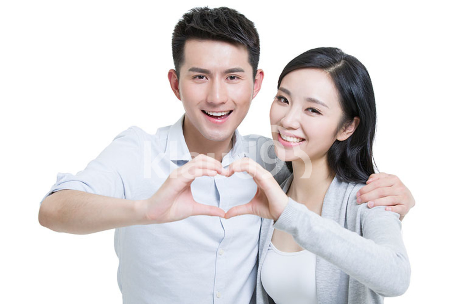 Happy young Chinese couple doing heart shape gesture