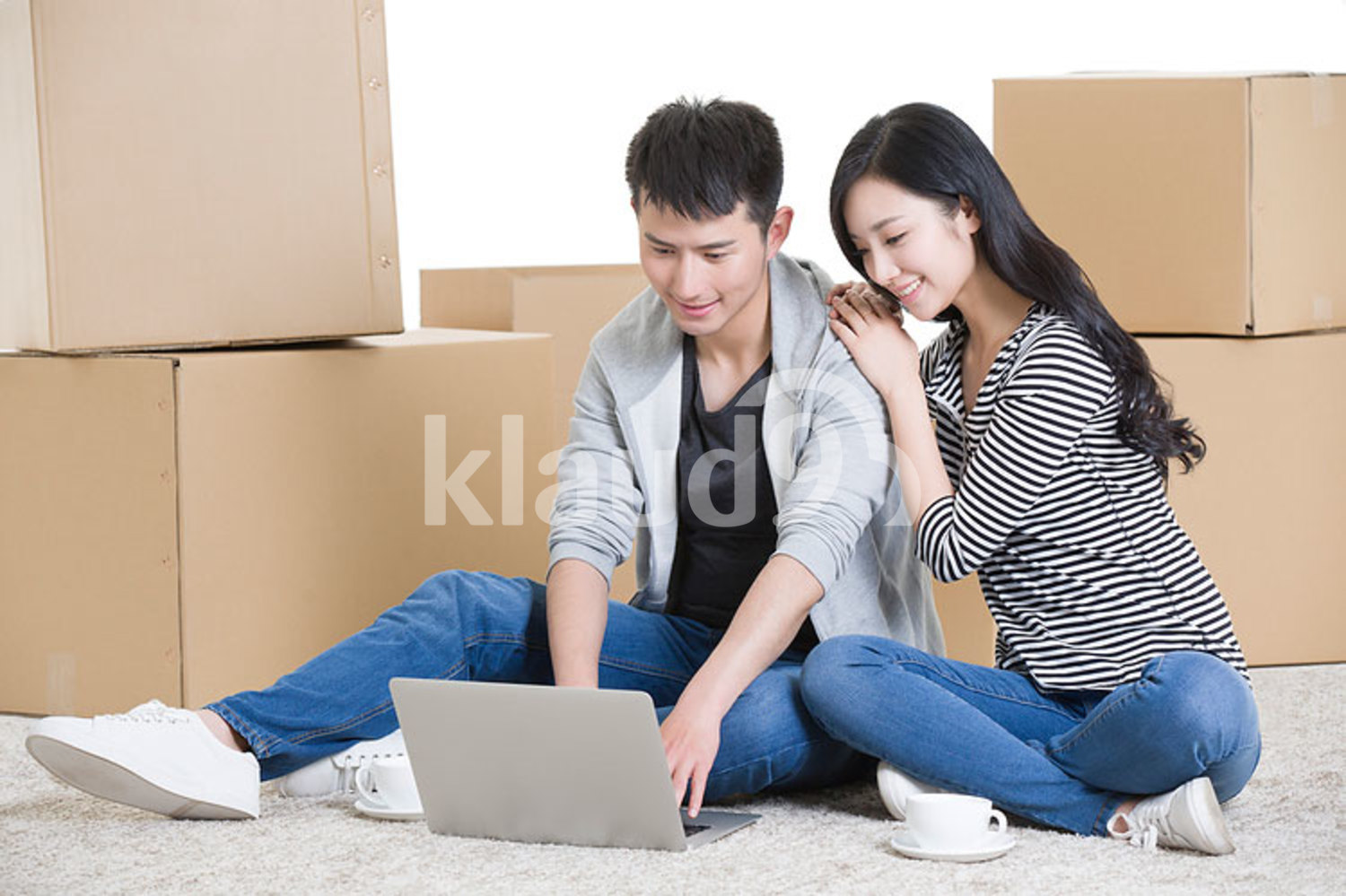 Young Chinese couple using laptop on floor