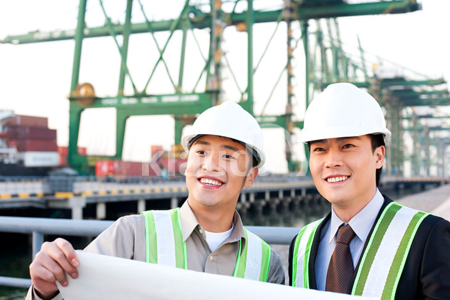 Chinese shipping industry professionals looking over blueprints
