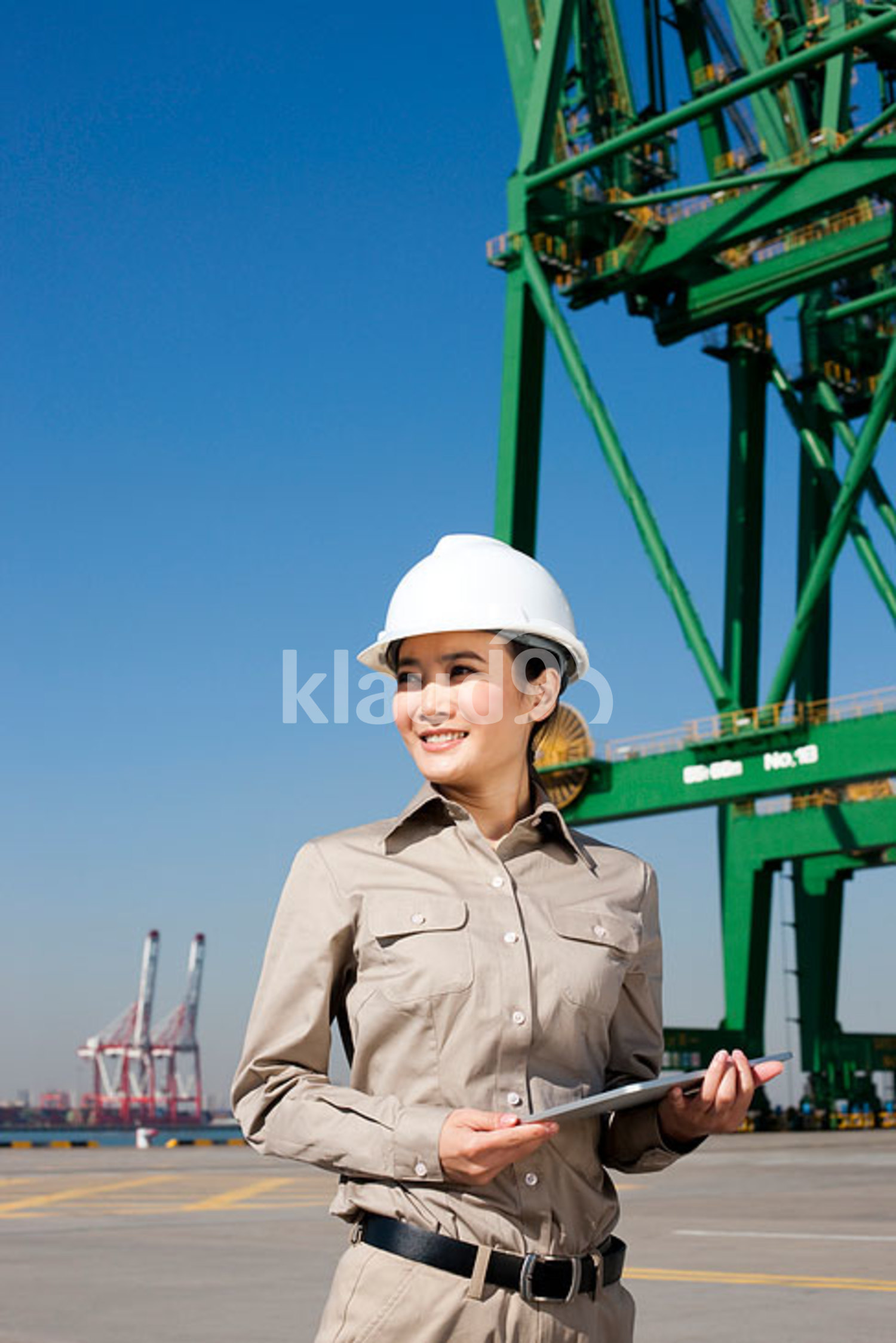 Female Chinese shipping industry worker with clipboard