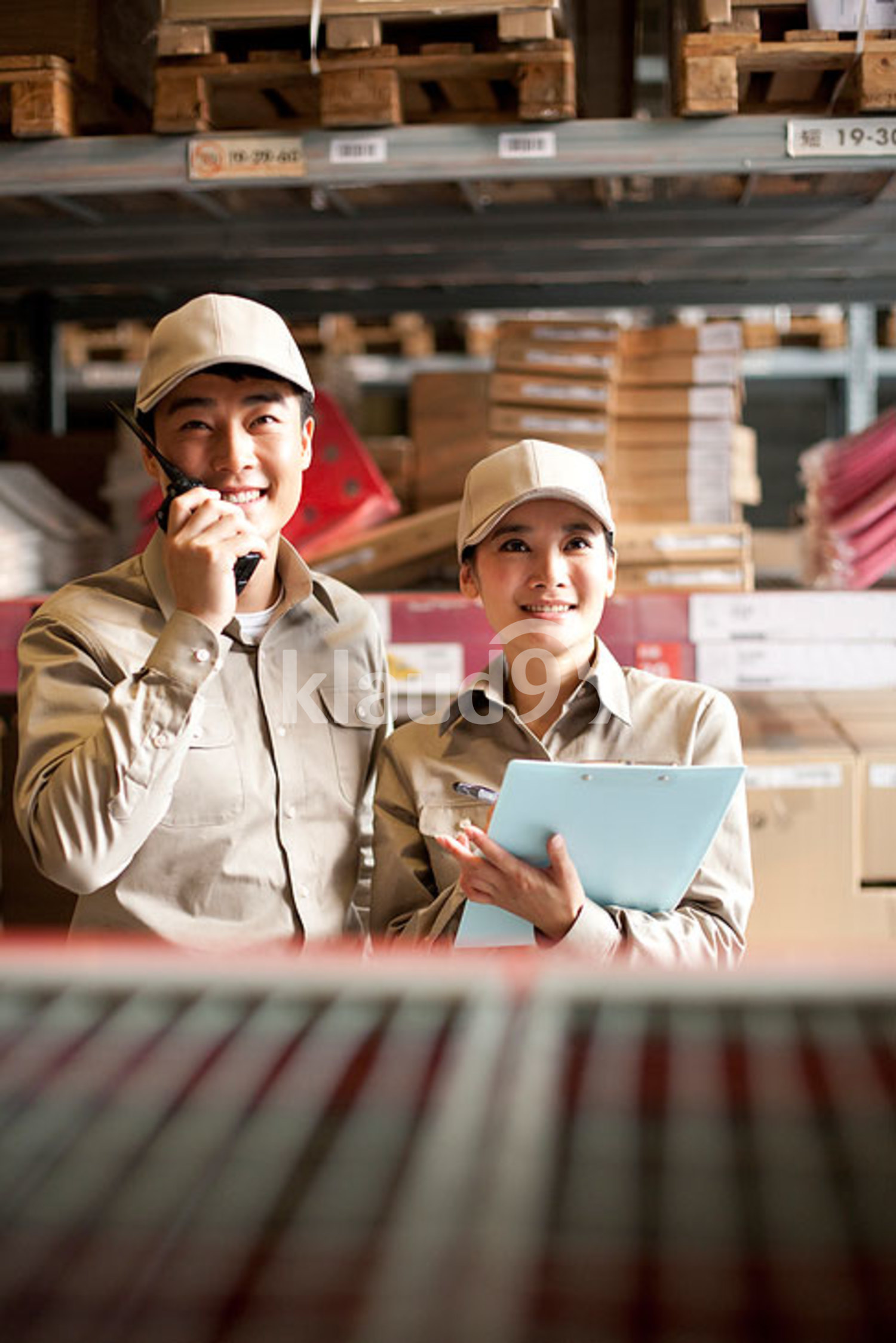 Male and female Chinese warehouse worker looking at boxes