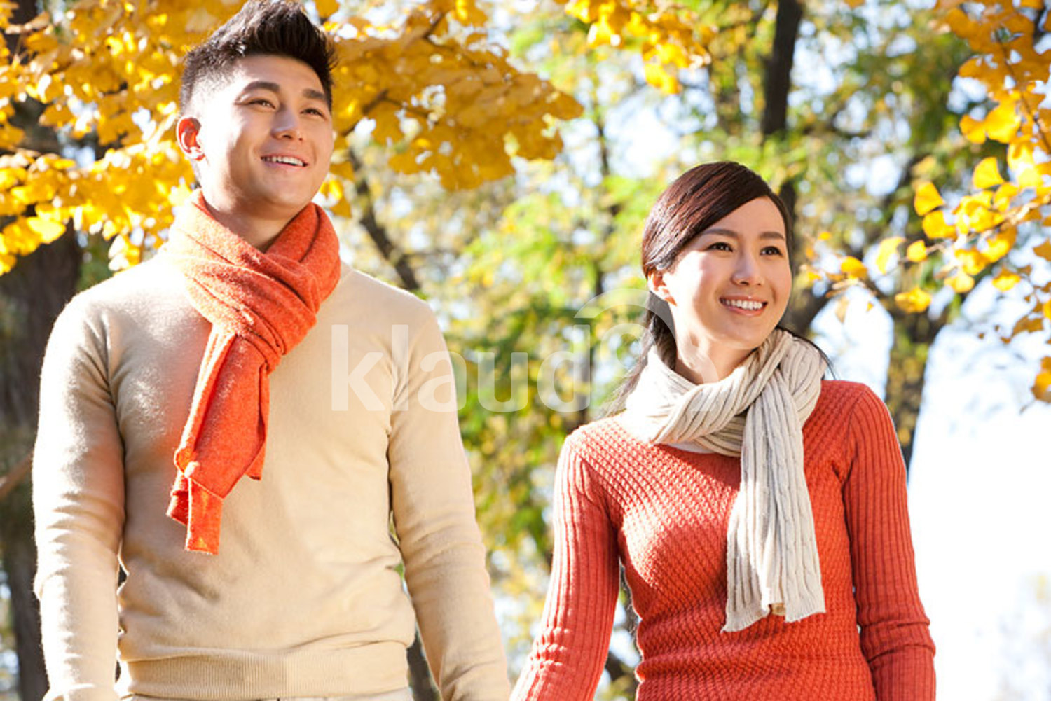 Young Chinese couple strolling through a park in autumn