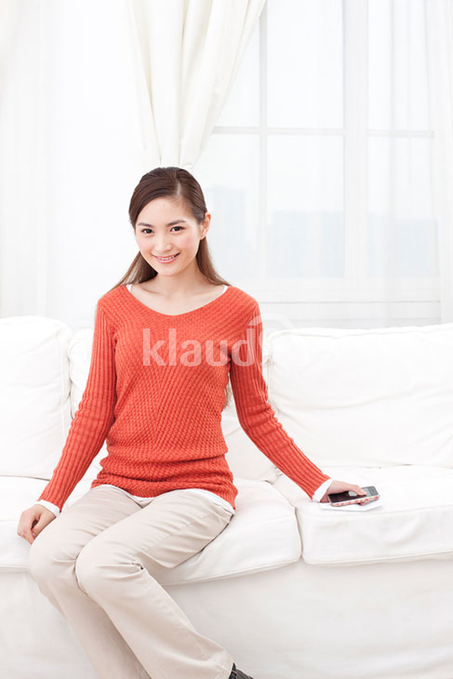 Young Chinese woman sitting in couch