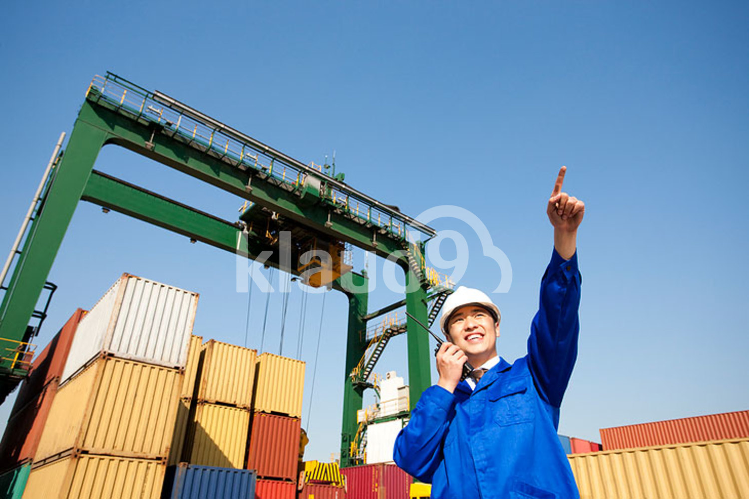 Chinese shipping industry manager with a walkie-talkie pointing