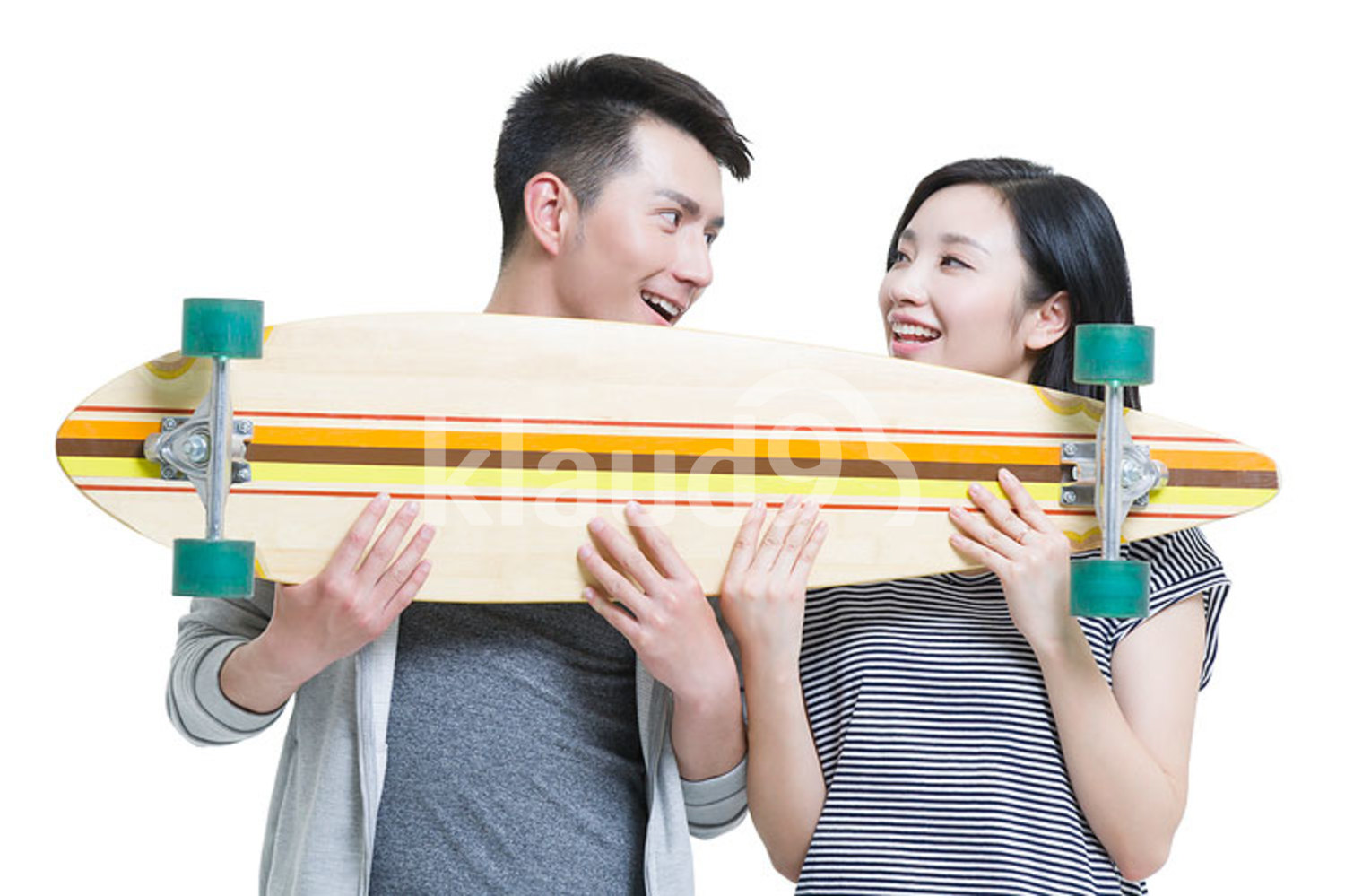 Happy young Chinese couple holding a skateboard