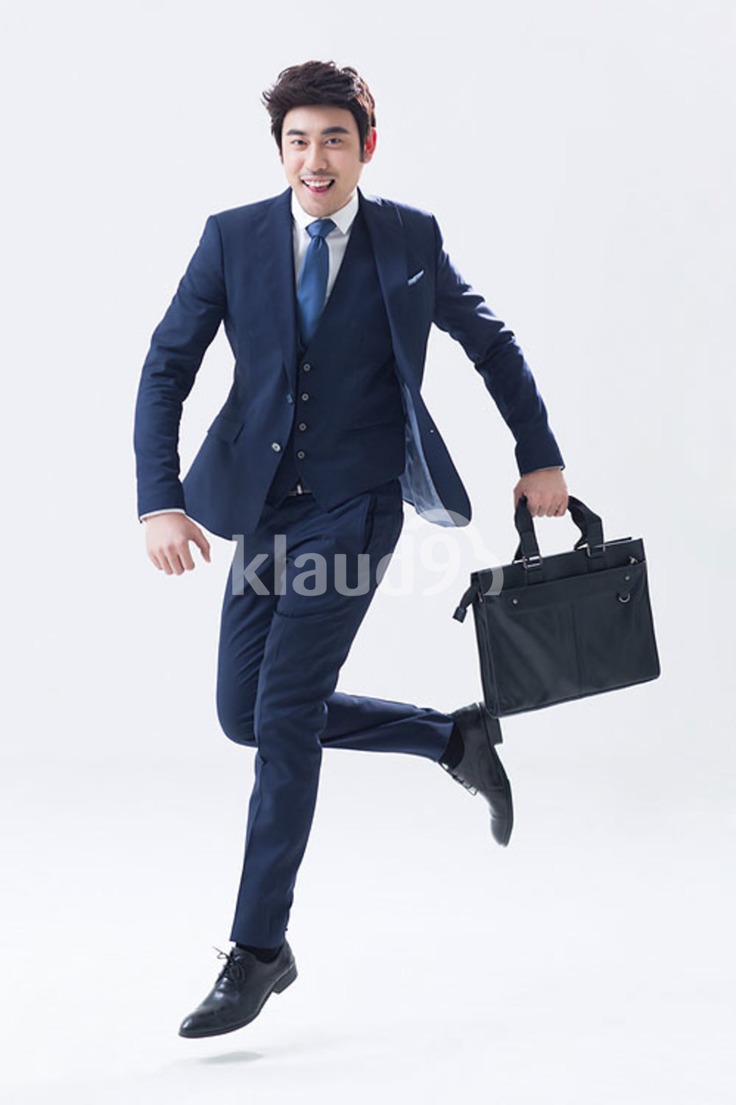 Young Chinese businessman running with briefcase