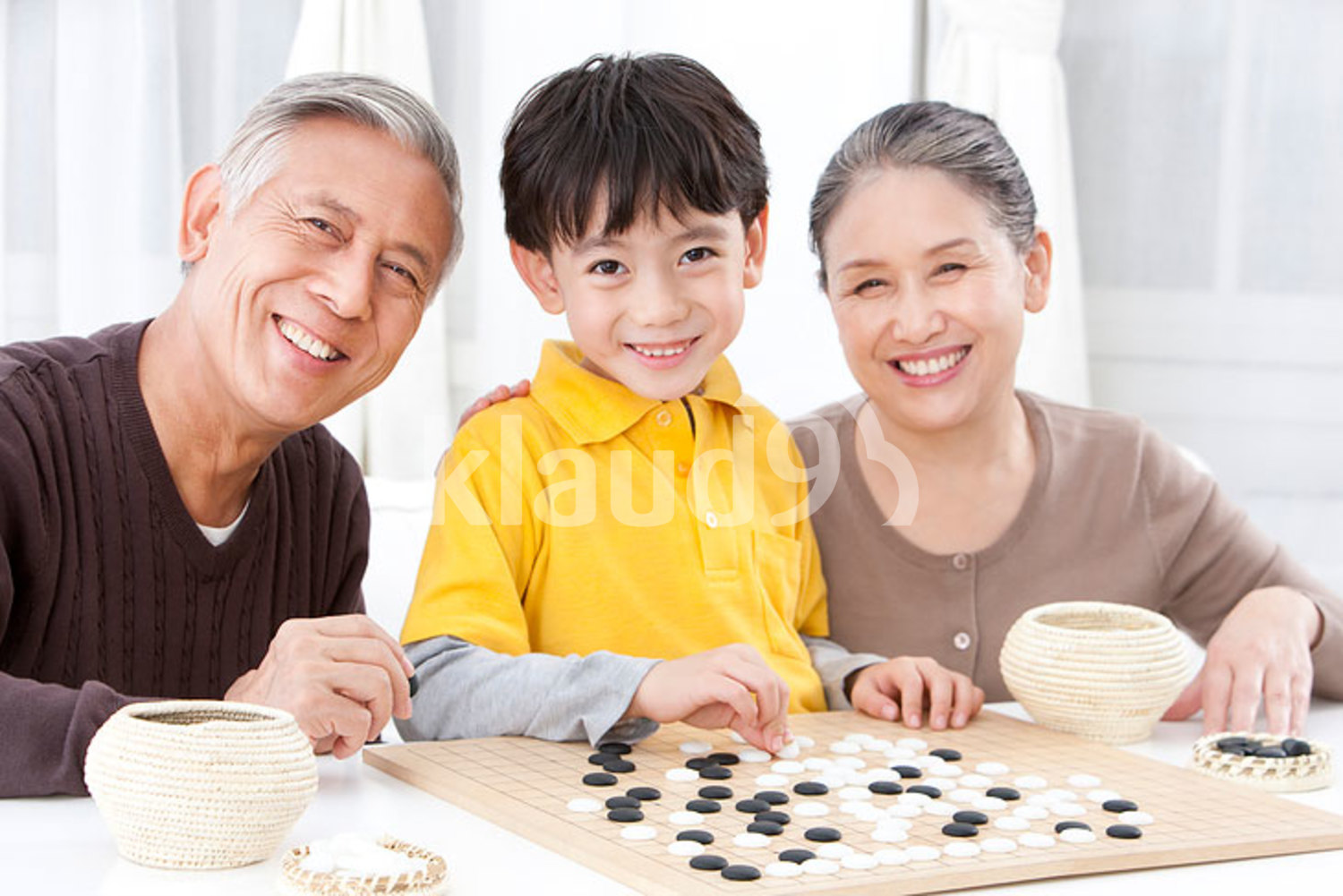 Chinese grandparents and grandson playing the game of Go