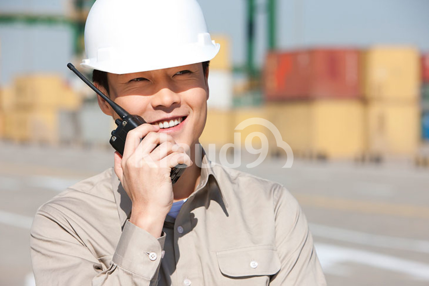 Male Chinese shipping industry worker with walkie-talkie