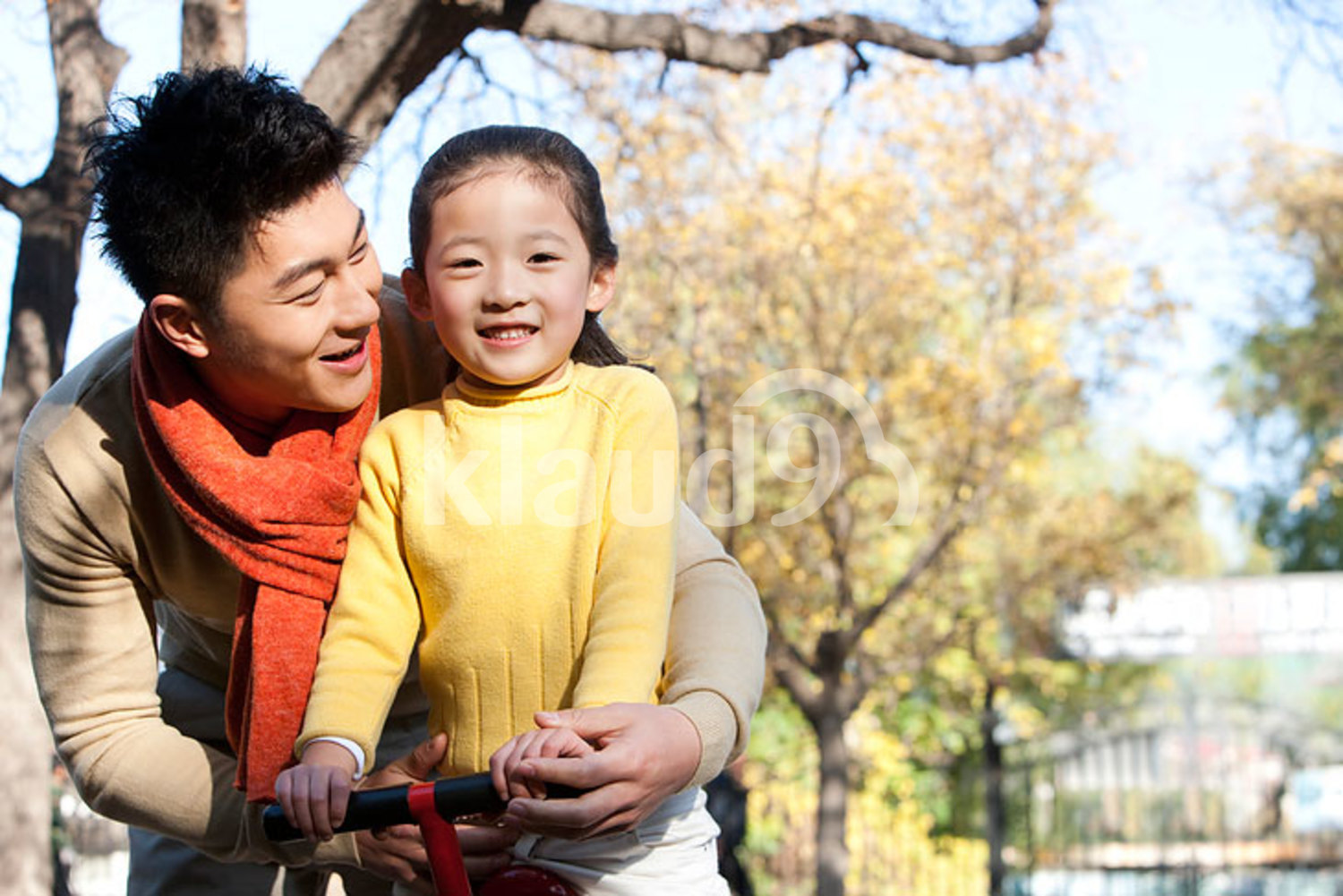 Chinese girl playing seesaw with her father