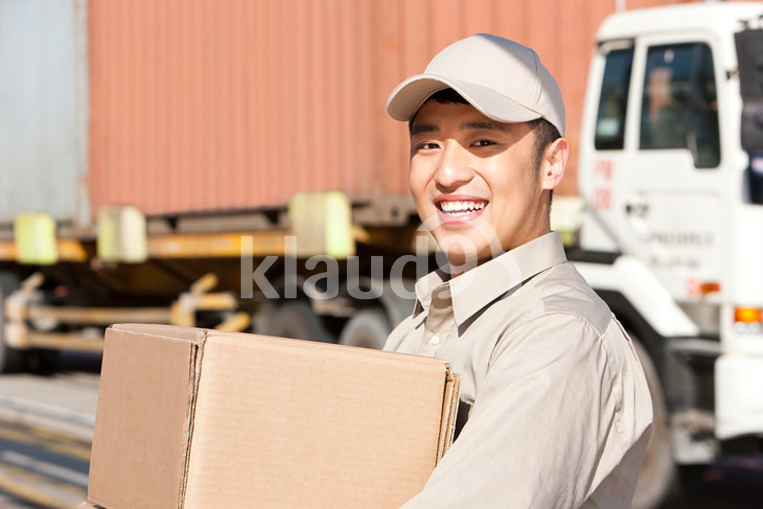 Chinese shipping industry worker carrying cardboard boxes