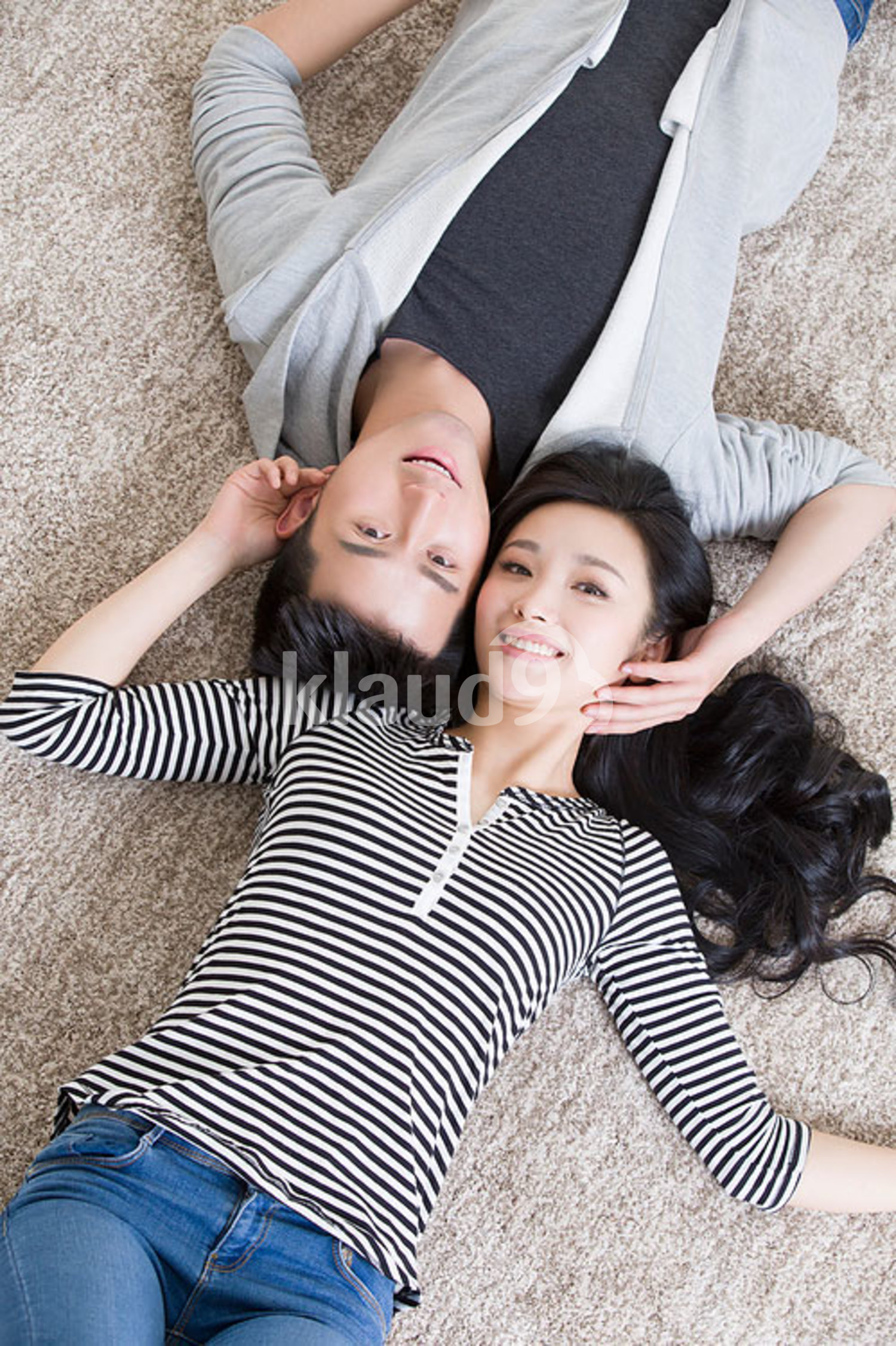 Young Chinese couple lying on floor