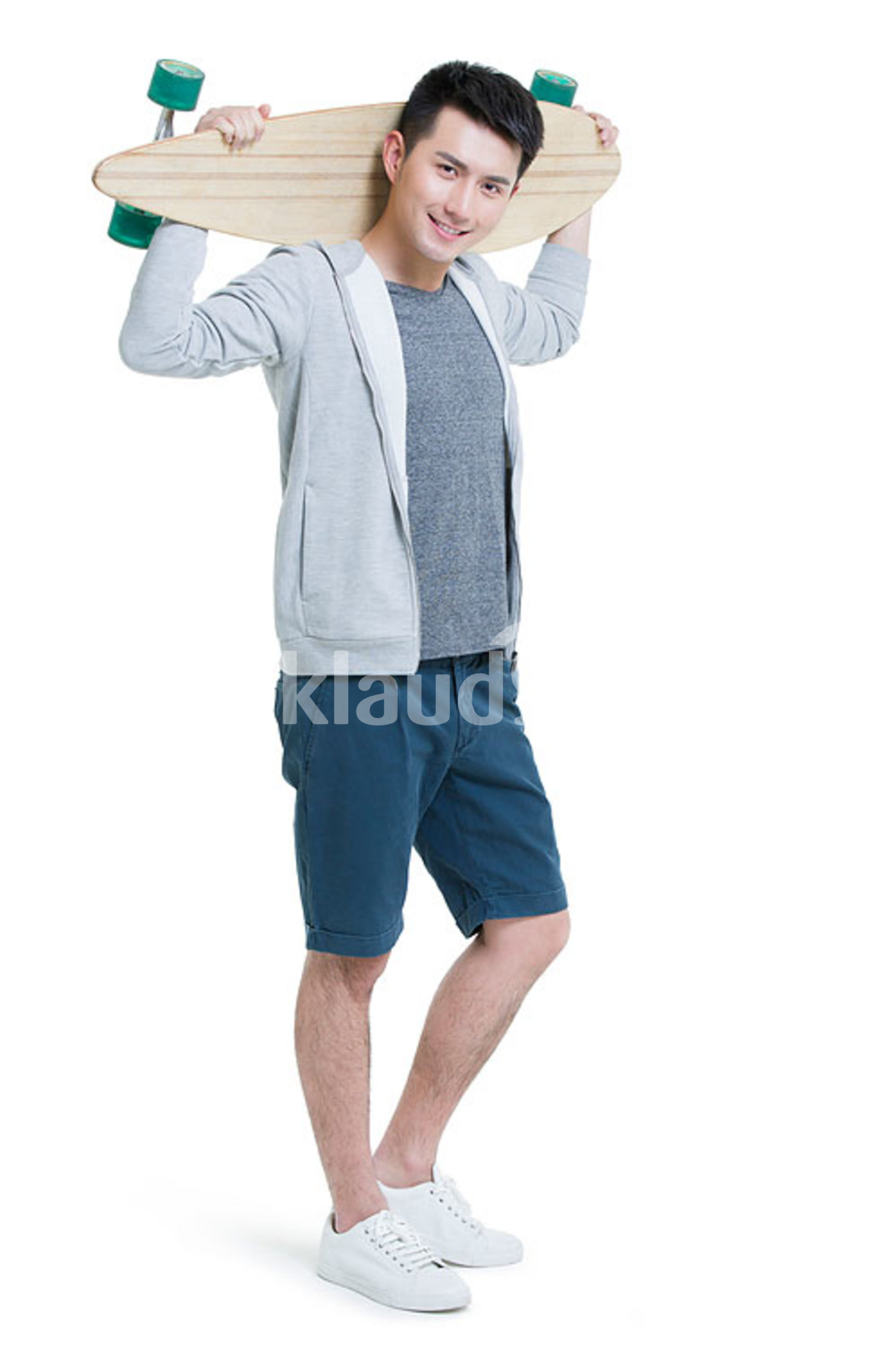 Happy young Chinese man holding a skateboard